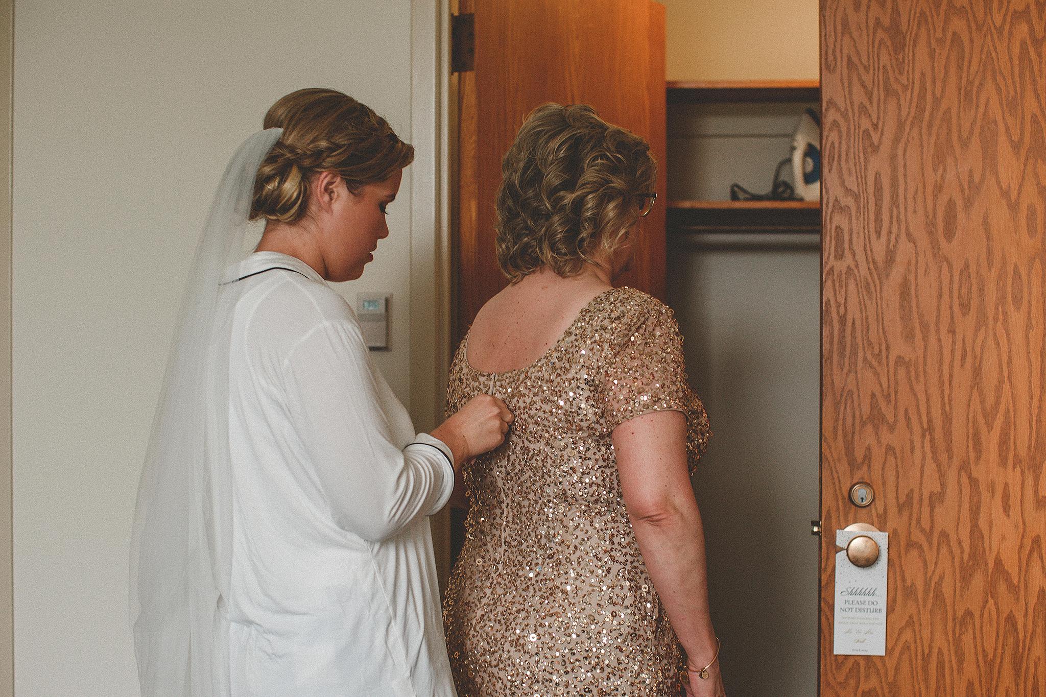 bride zipping up her mother's dress | dekalb, IL wedding photographer