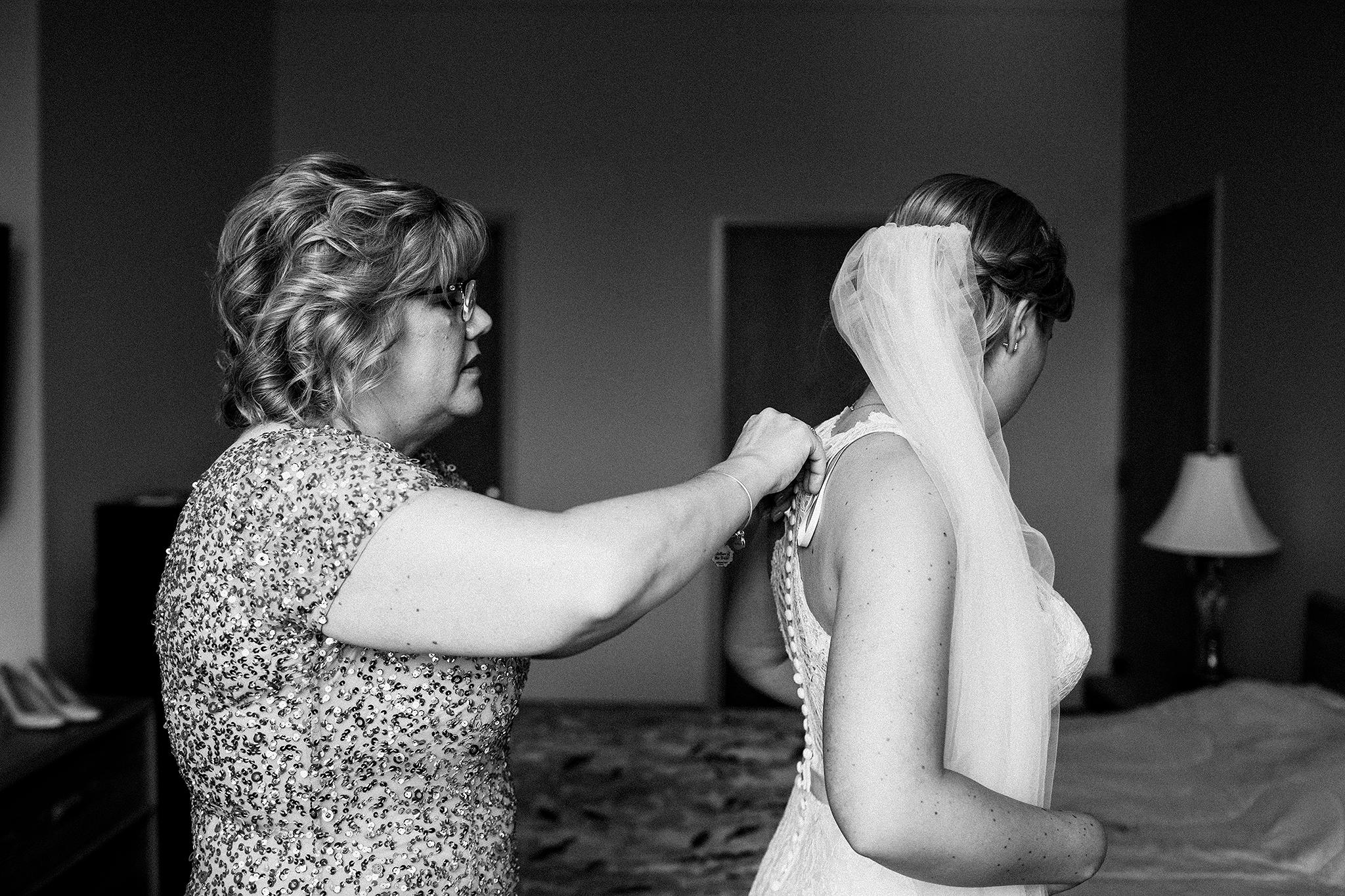 mom zipping up bride's wedding dress | dekalb, IL wedding photographer
