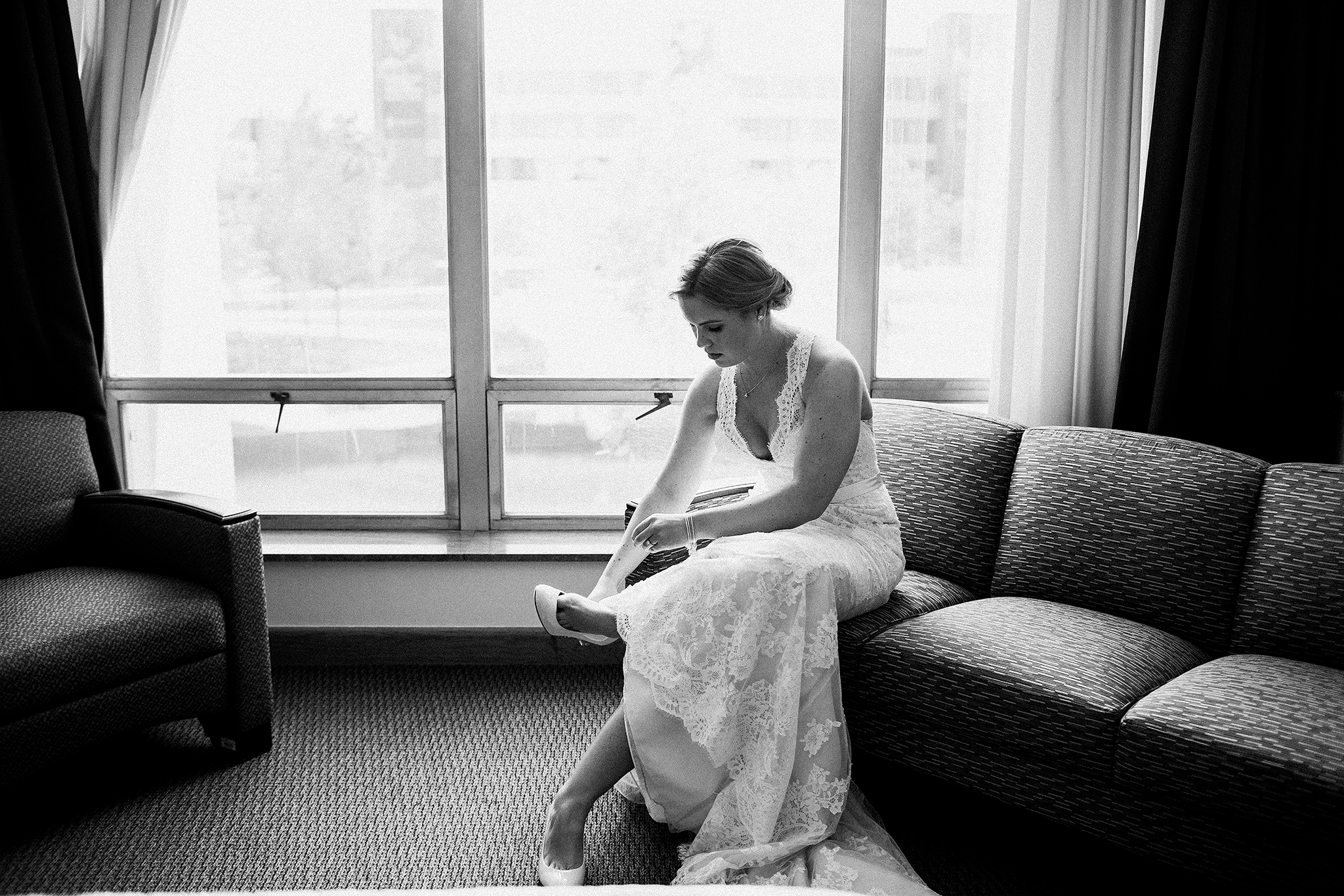 black and white image of bride putting on shoes | dekalb, IL wedding photographer