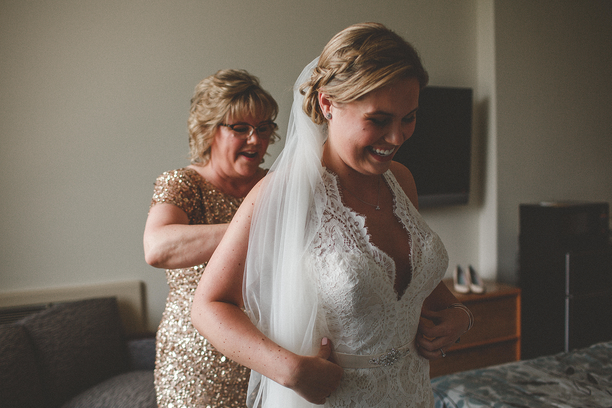 bride getting into wedding dress with mom zipping | dekalb, IL wedding photographer