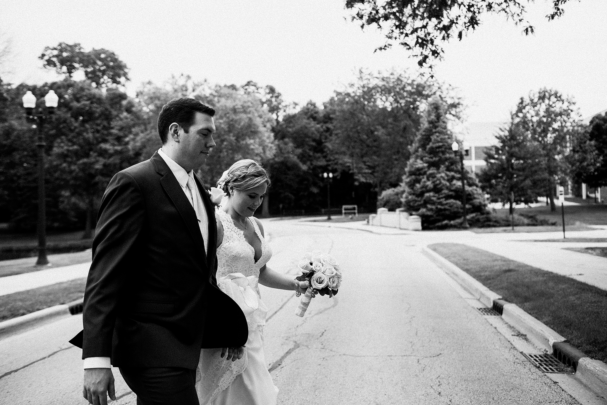 candid black and white image of bride and groom crossing street | dekalb, IL wedding photographer | chrissy deming