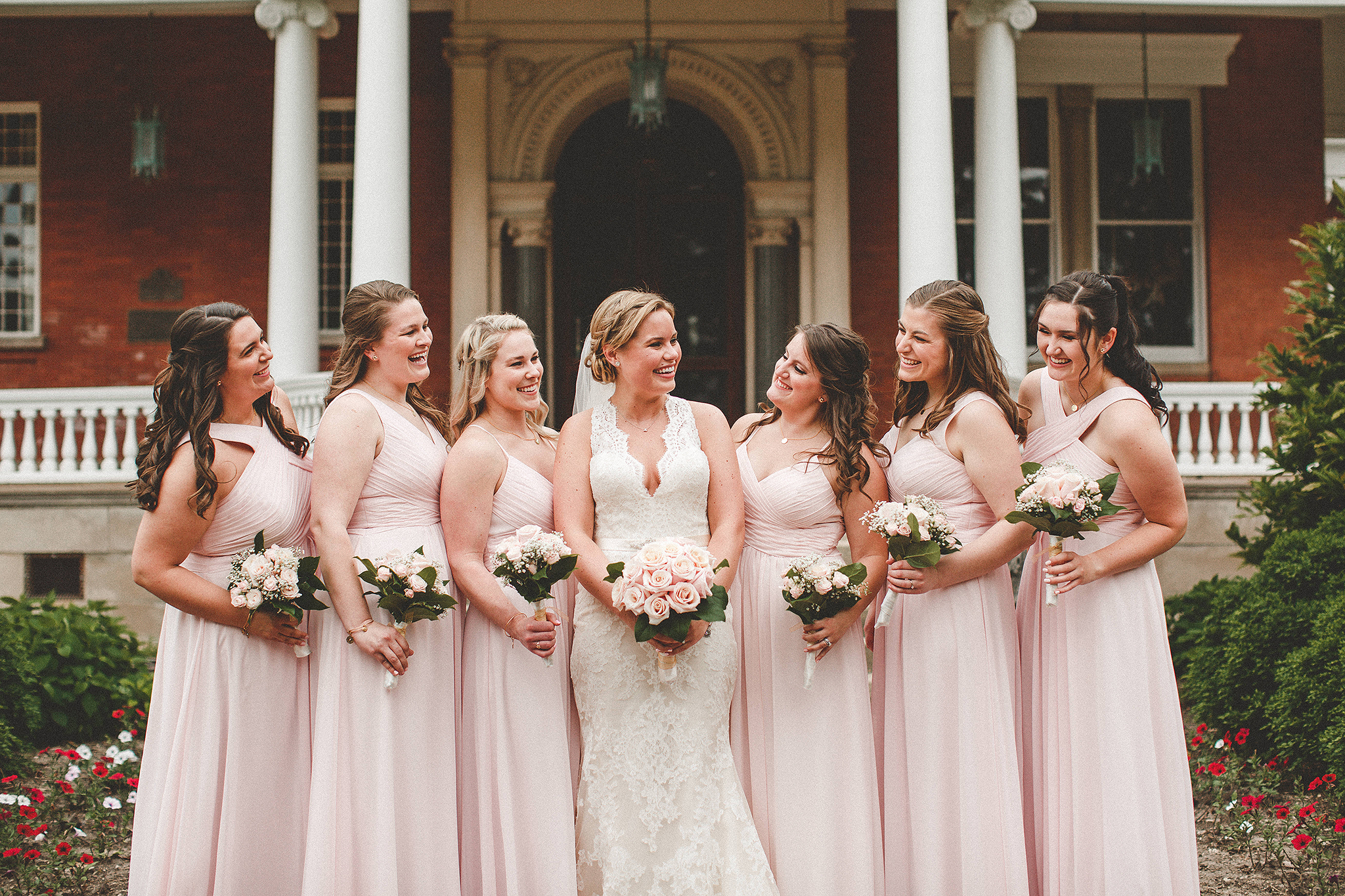 candid image of bride and bridesmaids laughing | dekalb, Il wedding photographer