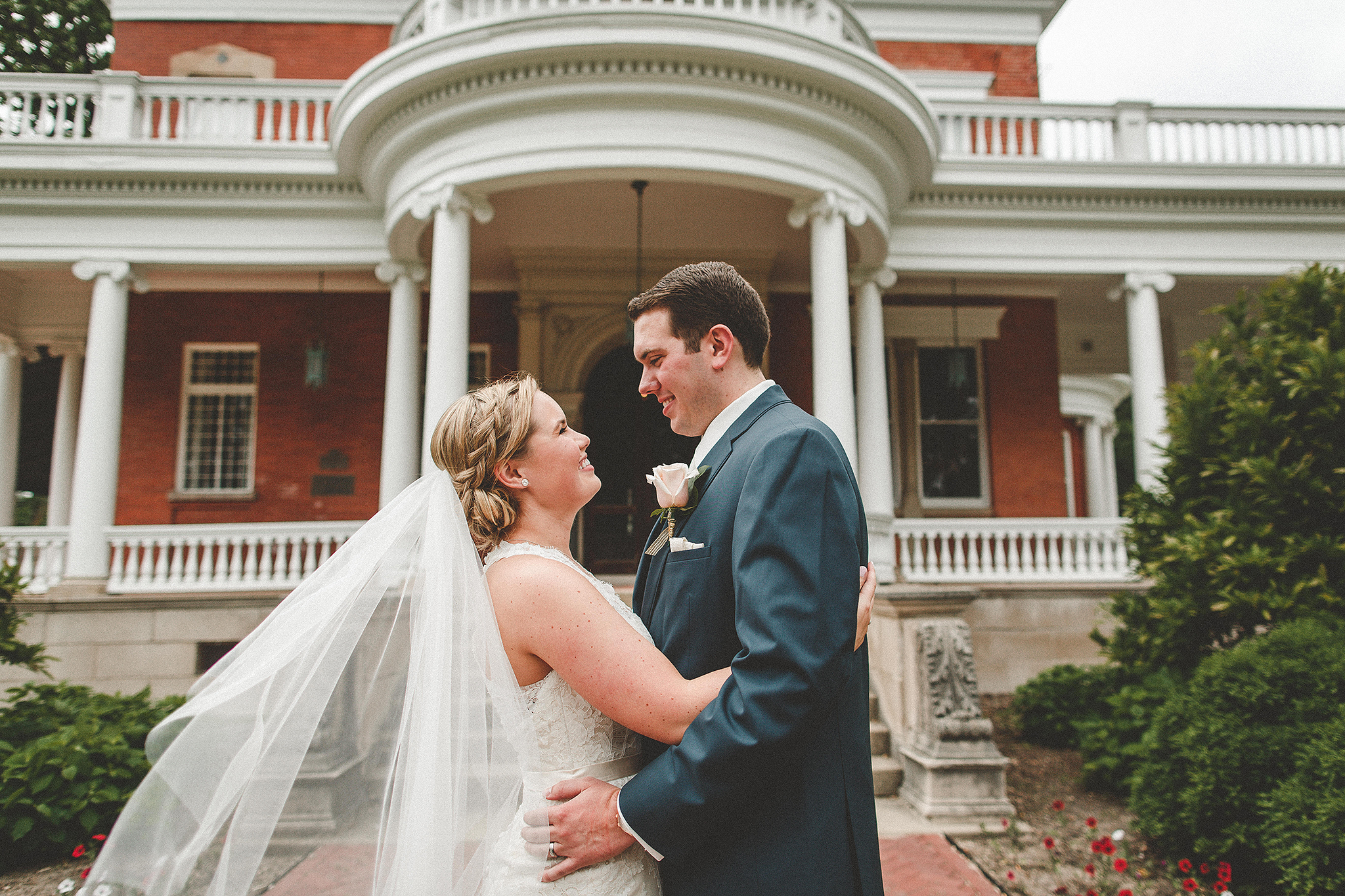 portrait of bride and groom facing each other smiling, veil blowing | ellwood house, dekalb, il photographer