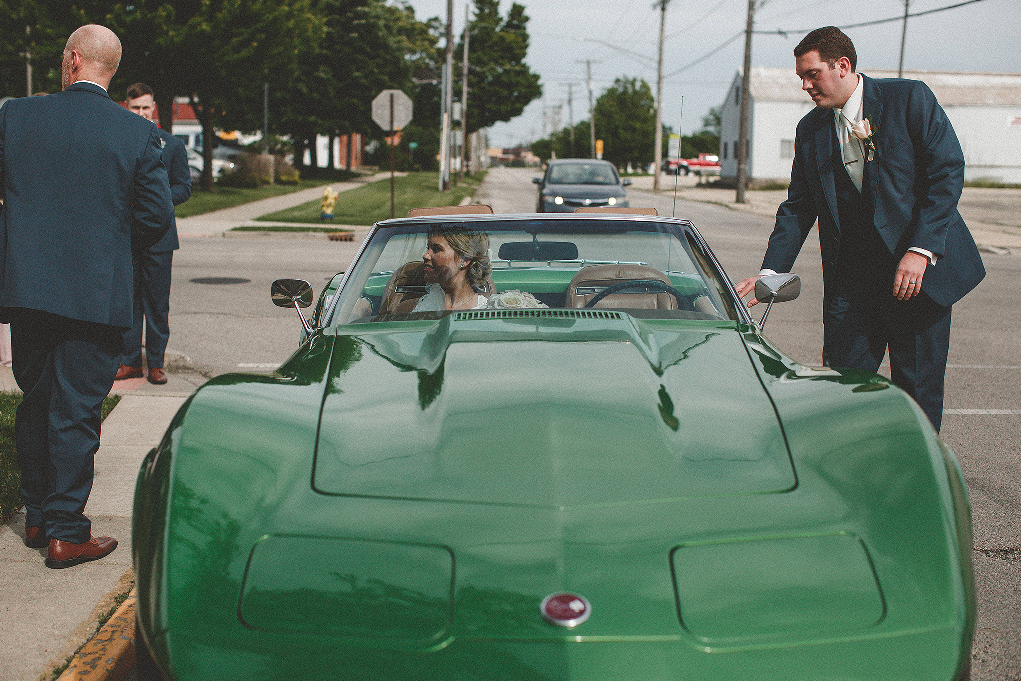 bride and groom getting into green classic 75 corvette stingray | dekalb, il wedding photographer