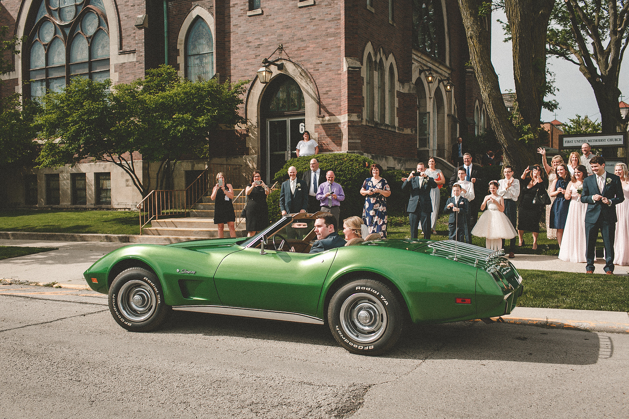 bride and groom driving off in green classic 75 corvette stingray | dekalb il wedding photographer