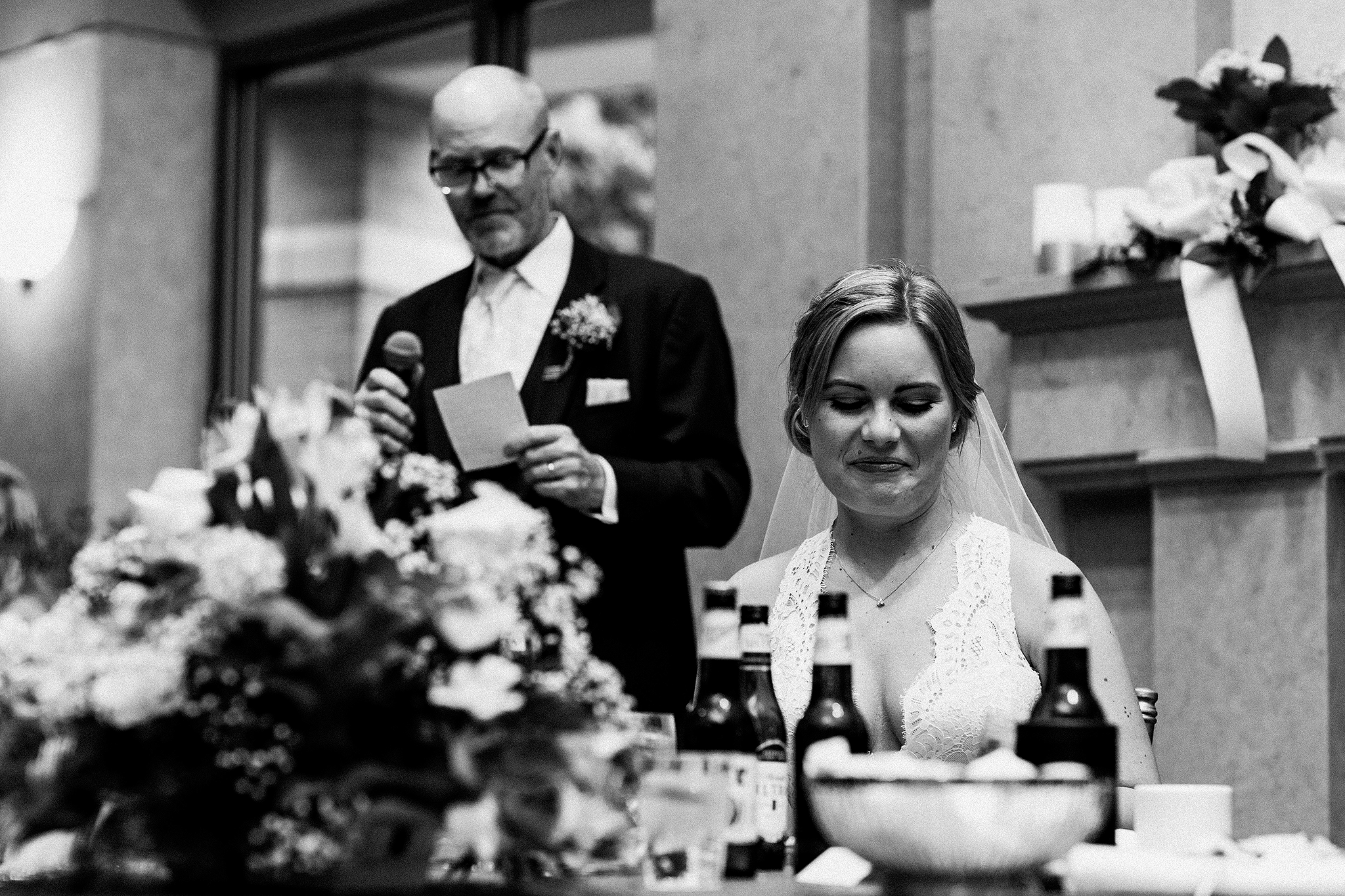 father of the bride speech with bride in the foreground smiling | dekalb, il wedding photographer
