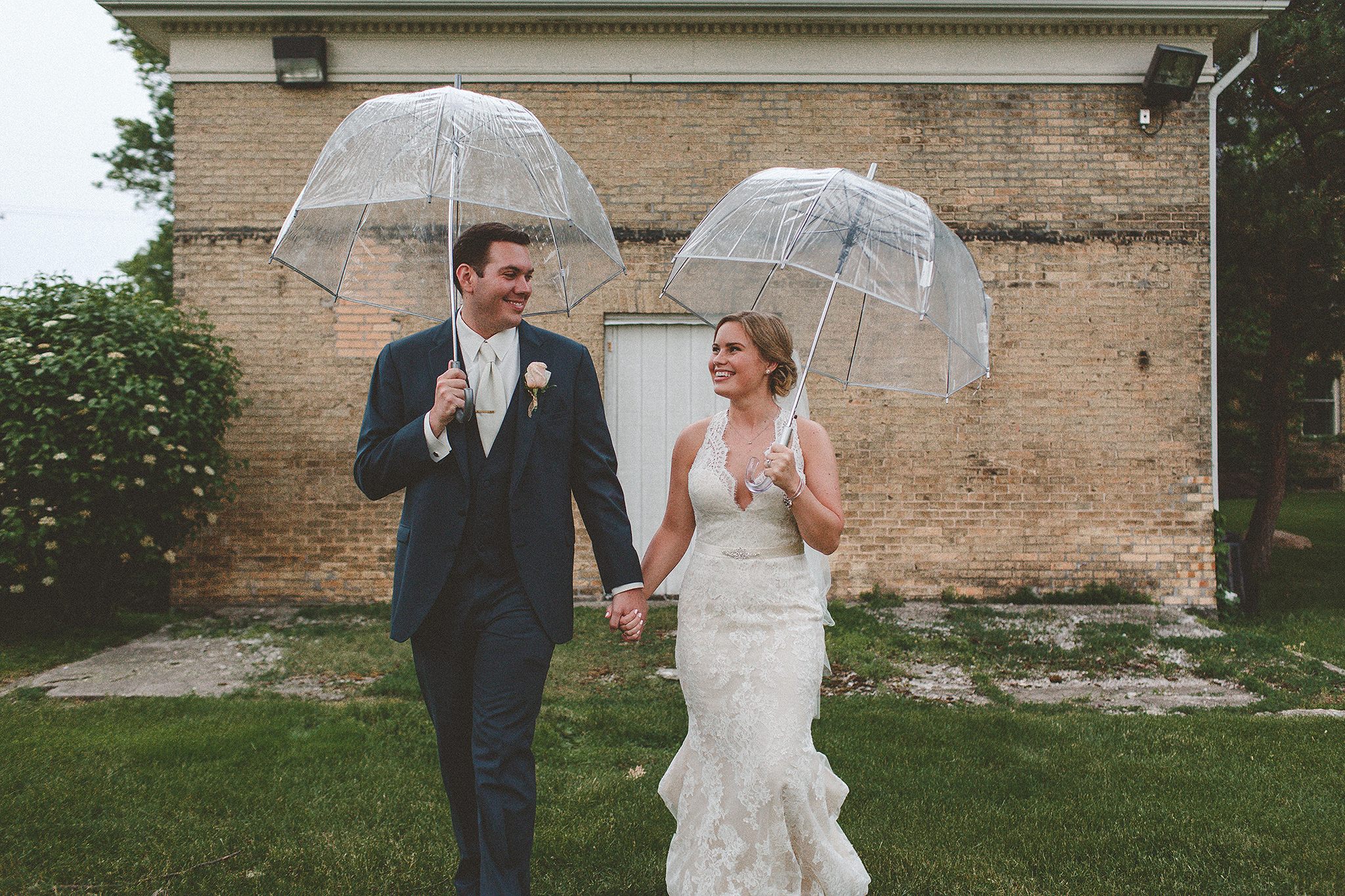 bride and groom holding clear umbrellas, walking towards camera, looking at each other | dekalb IL photographer
