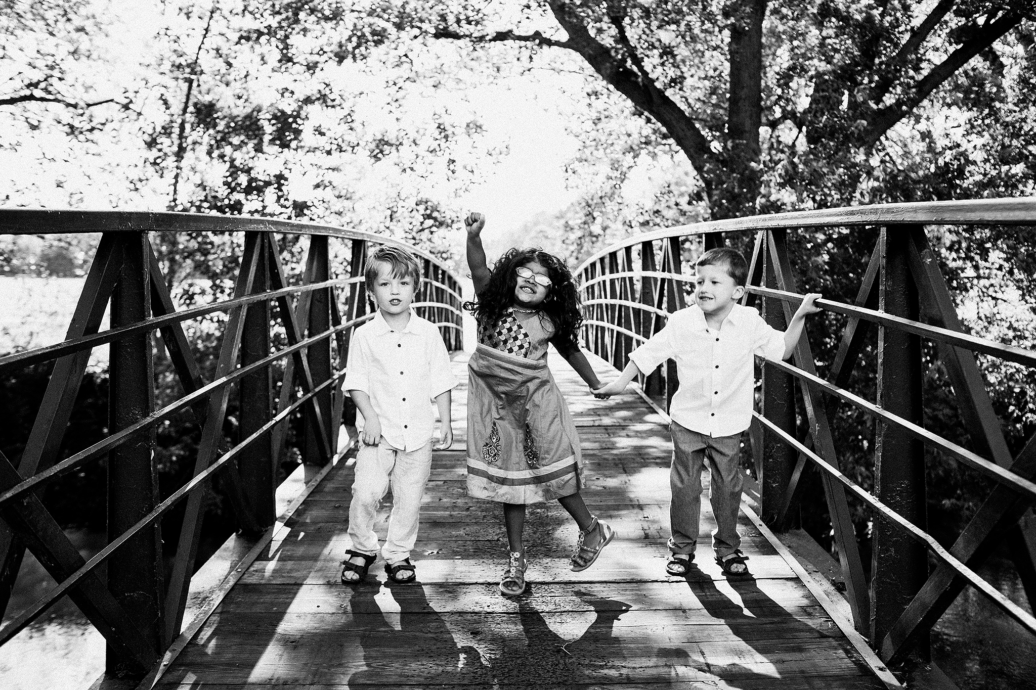 two brothers with girl cousin dancing on bridge | extended family photos outside | sycamore il family photographer