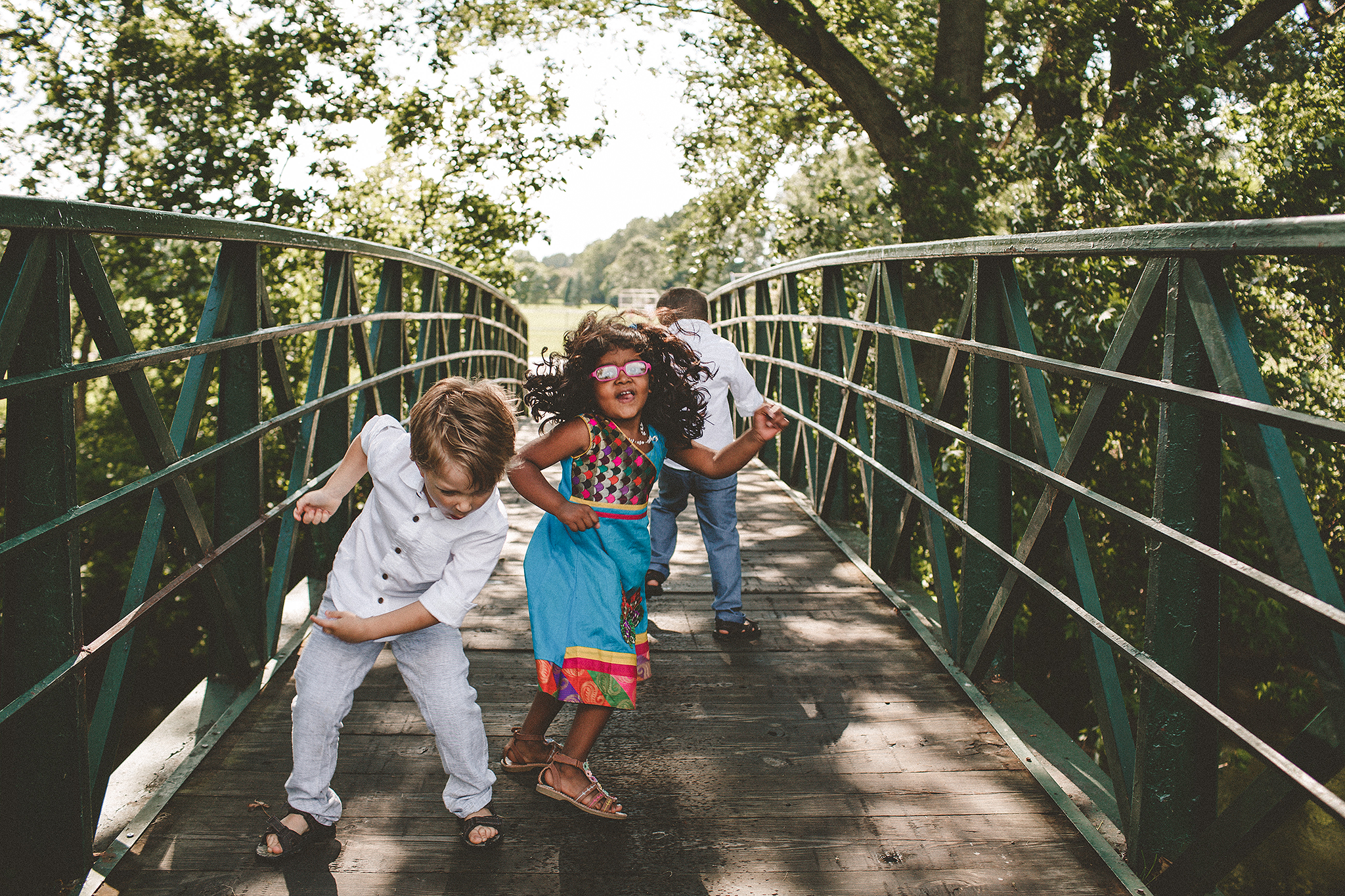 two brothers with girl cousin dancing on bridge | family photos outside | sycamore il family photographer