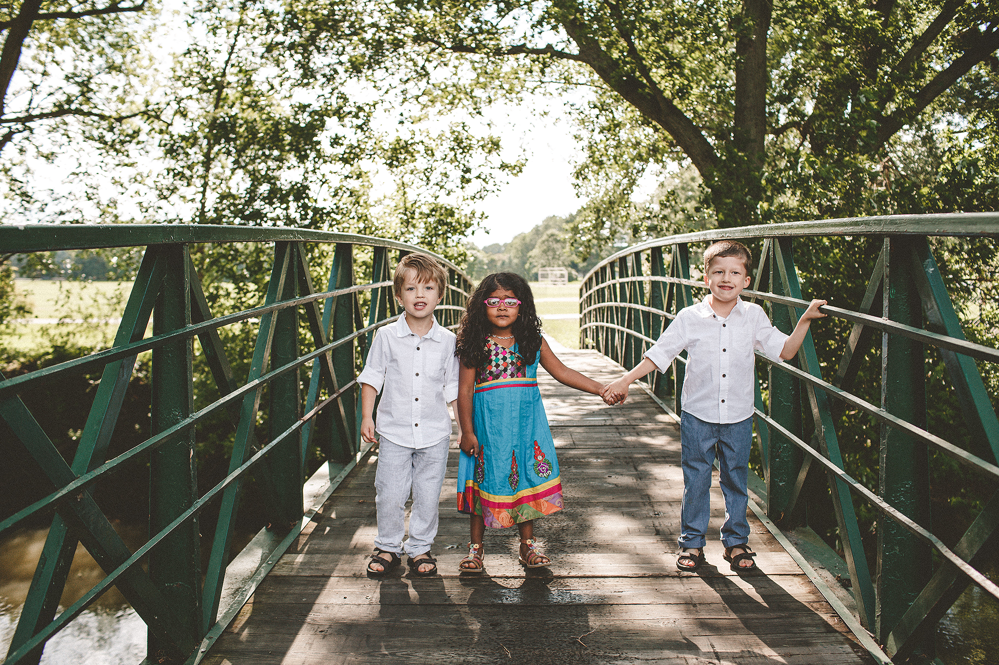 two brothers with girl cousin on bridge | extended family photos outside | sycamore il family photographer