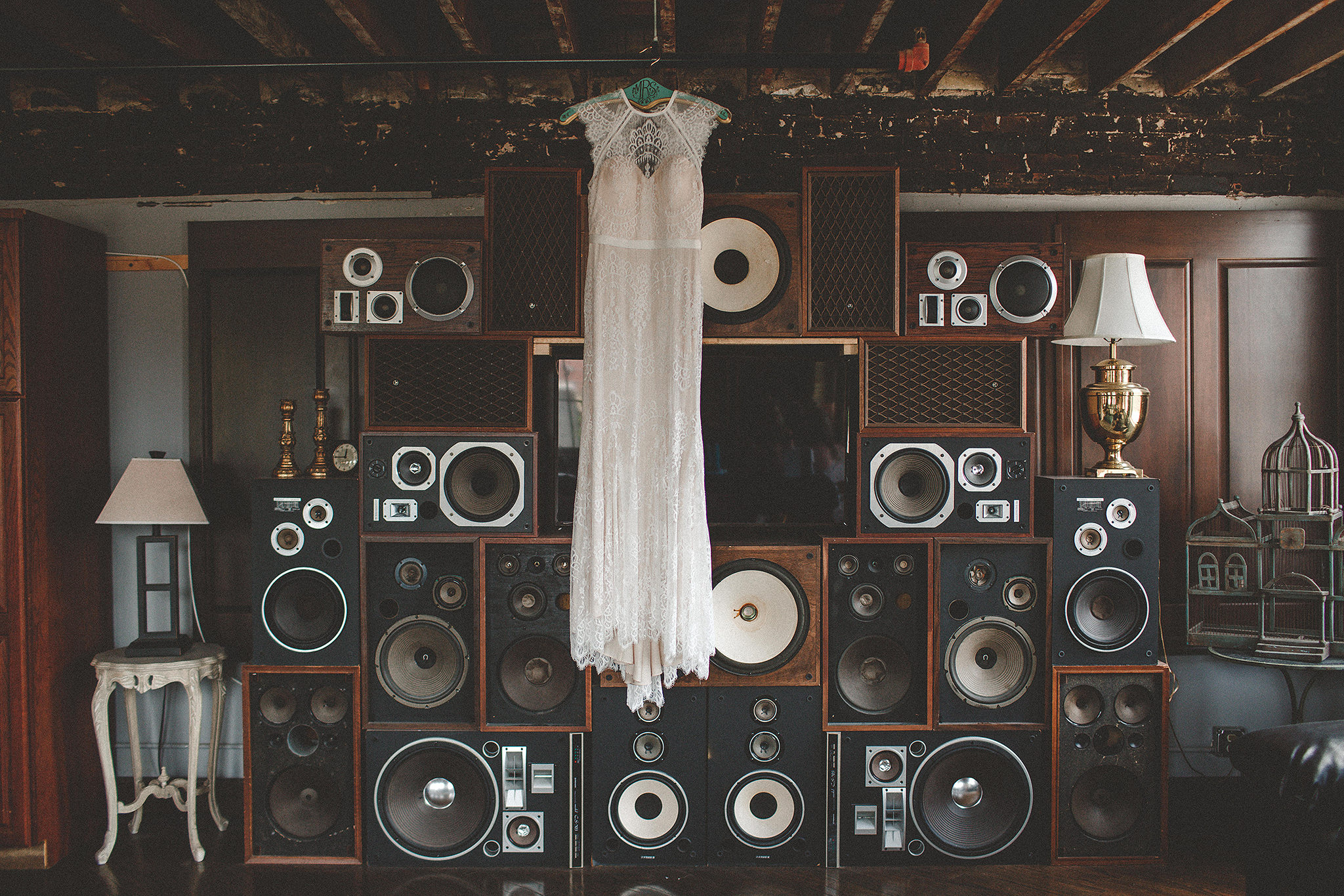 wedding dress hanging in front of vintage speaker wall | ivy house milwaukee photographer | chrissy deming