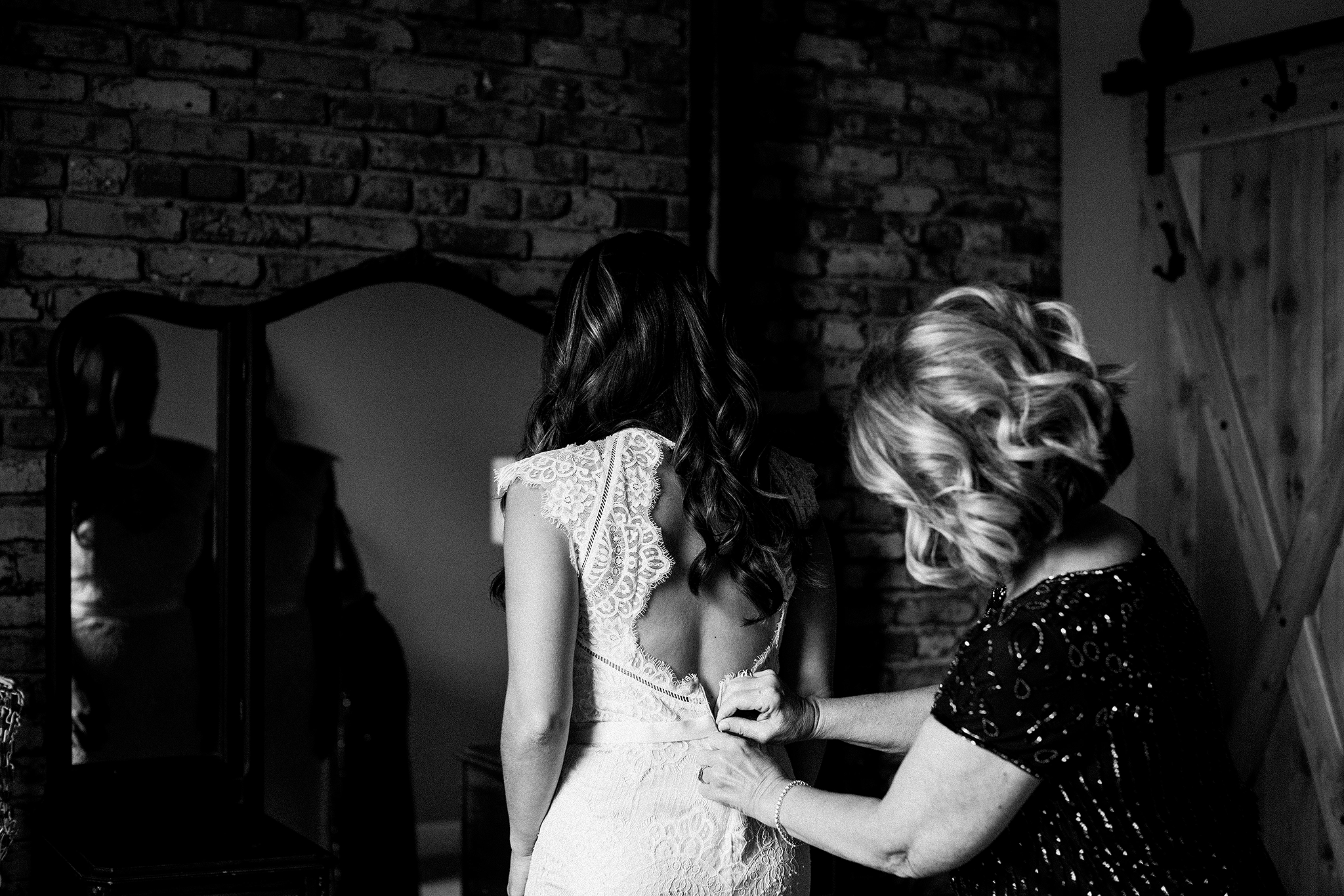 bride getting into wedding dress, mother of the bride zipping up dress | the ivy house milwaukee