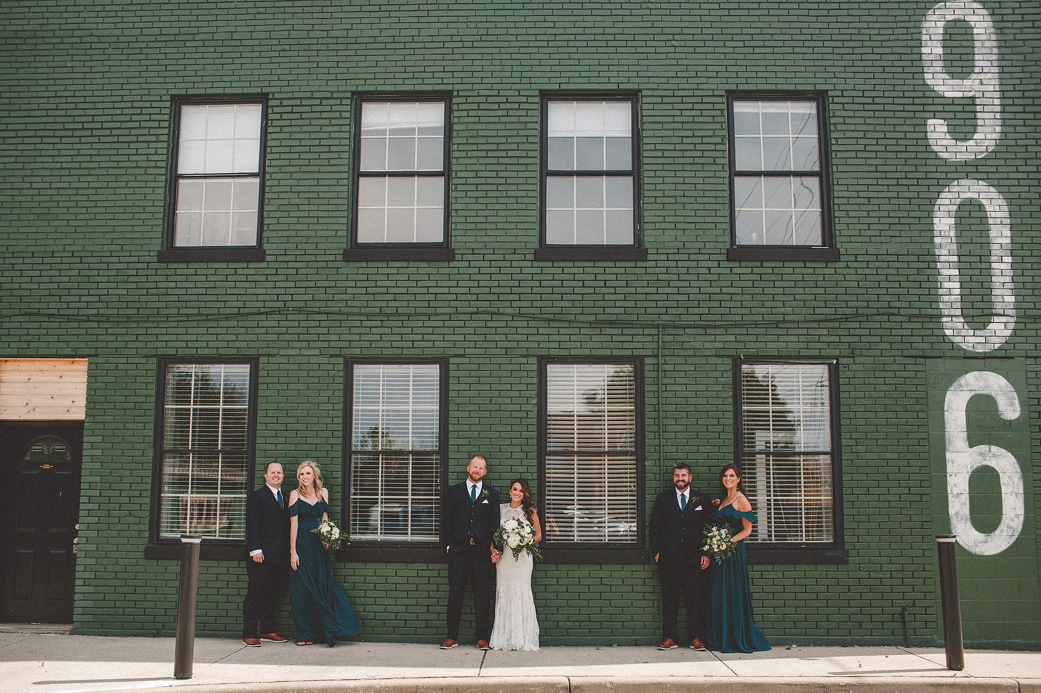 wedding party in front of green brick wall | the ivy house milwaukee wedding photographer | chrissy deming