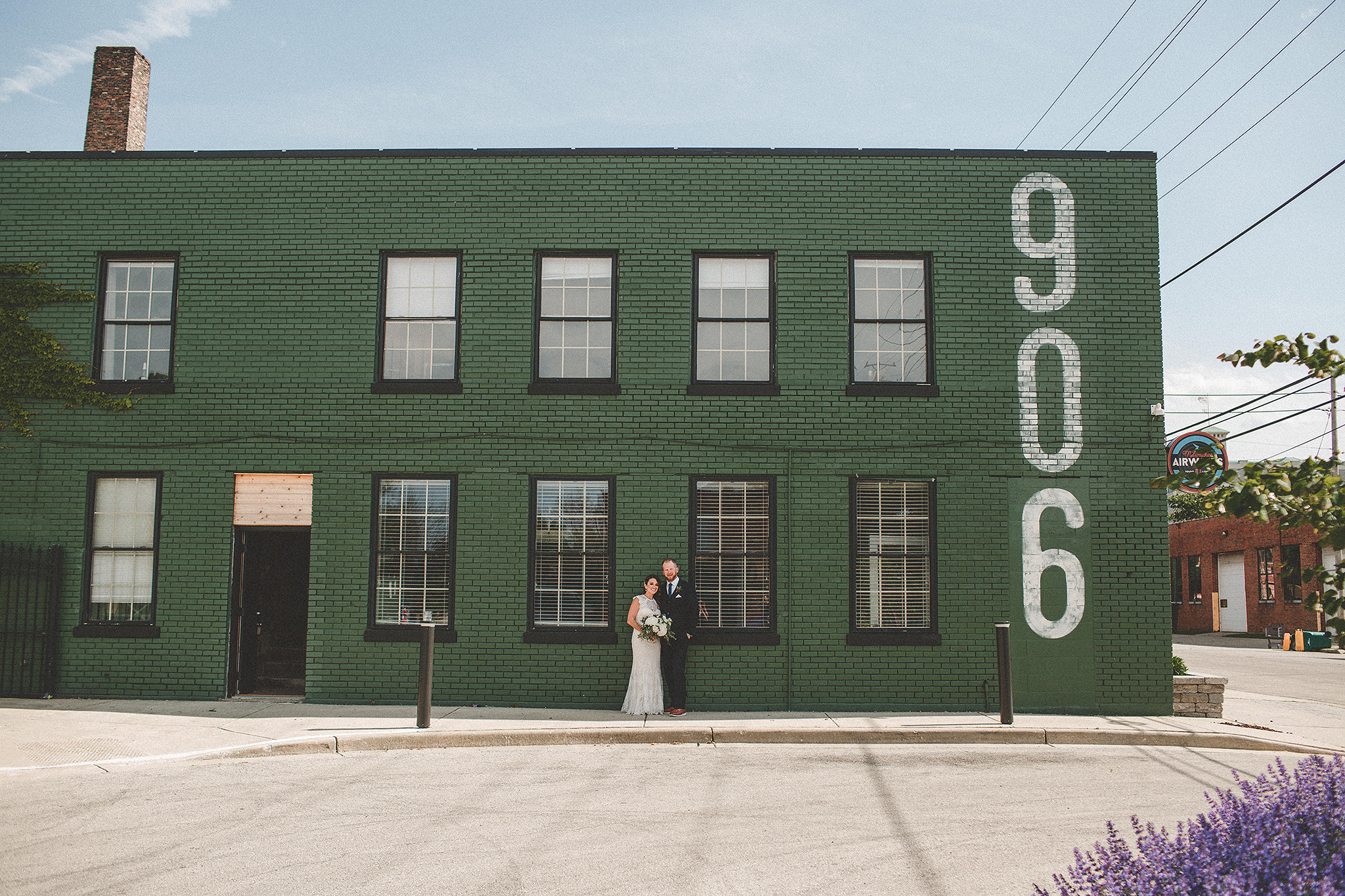 bride/groom in front of green brick wall | the ivy house milwaukee wedding photographer | chrissy deming