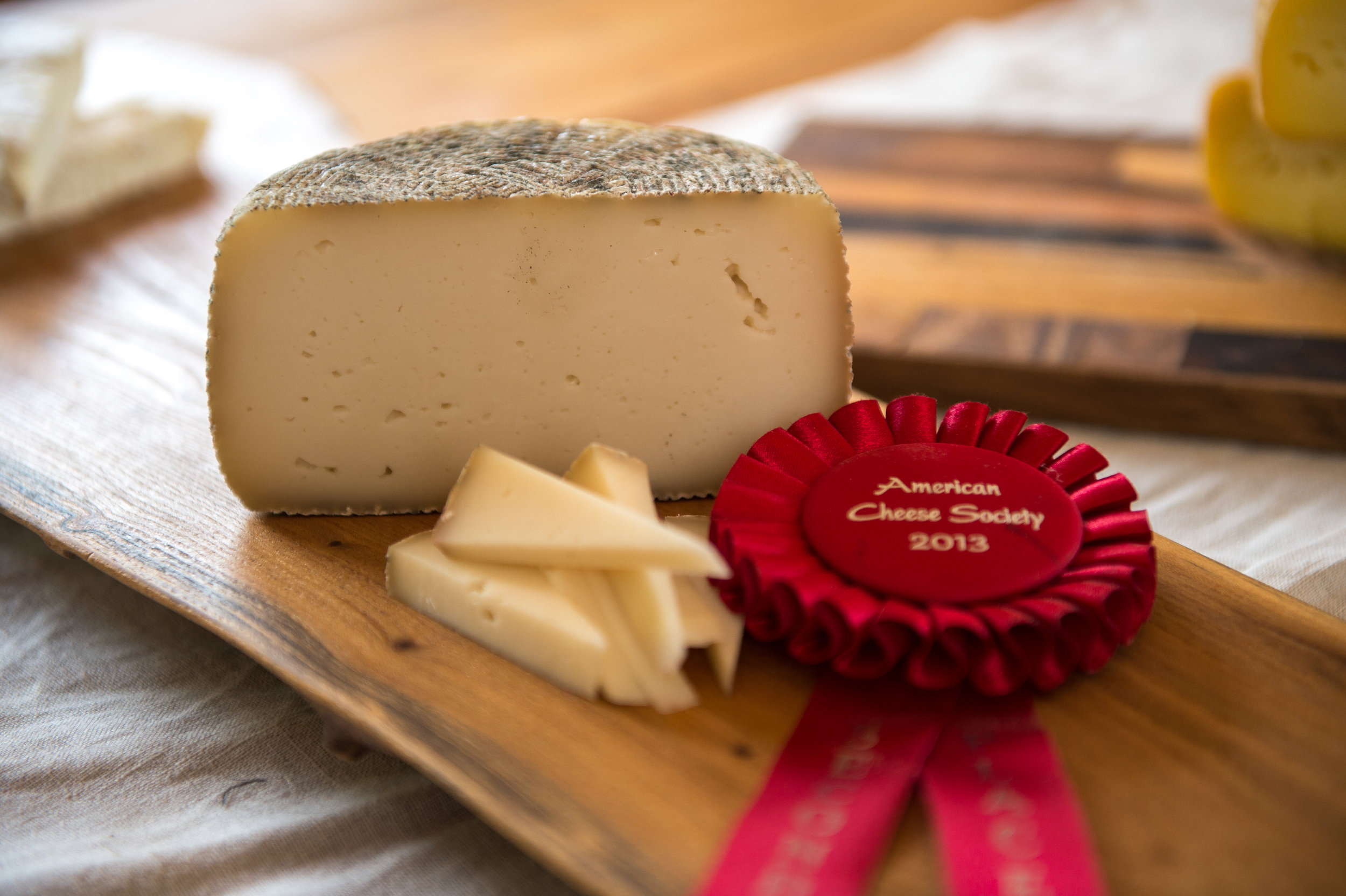 Esmontonian    2nd Place, American Cheese Society, American Made/International Style 2013   Raw goat's milk  Natural rind, semi-firm, enzymatic  Kid rennet  Aged on farm minimum 60 days  2.2 pounds (average weight) per wheel  Caromont Farm is close to the tiny village of Esmont – one road, no stoplight, and the kind of small town post office of a bygone era. This cheese is named for our home town. A small rustic tomme, made in an Italian basket mould. The Esmontonian begins with notes of minerality, a touch of citrus, and finishes with a delicate earthy aroma and a toasted maple note. With age expect a more picante note and a dry grana like texture.