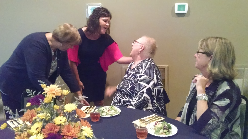 A snapshot from a past volunteer banquet, Bachman visits with some of her volunteers and shares a laugh with Bonnie Schoppman.