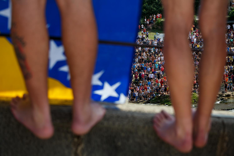 Two divers standing on the parapet of the Old Bridge behind the flag of Bosnia and Herzegovina as the national anthem is struck up.     Dva skakača stoje na zidu Starog mosta iza zastave Bosne i Hercegovine tokom intoniranja himne Bosne i Hercegovine.