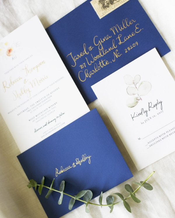 pointed pen calligraphy - In copperplate gold ink, against navy blue envelopes.