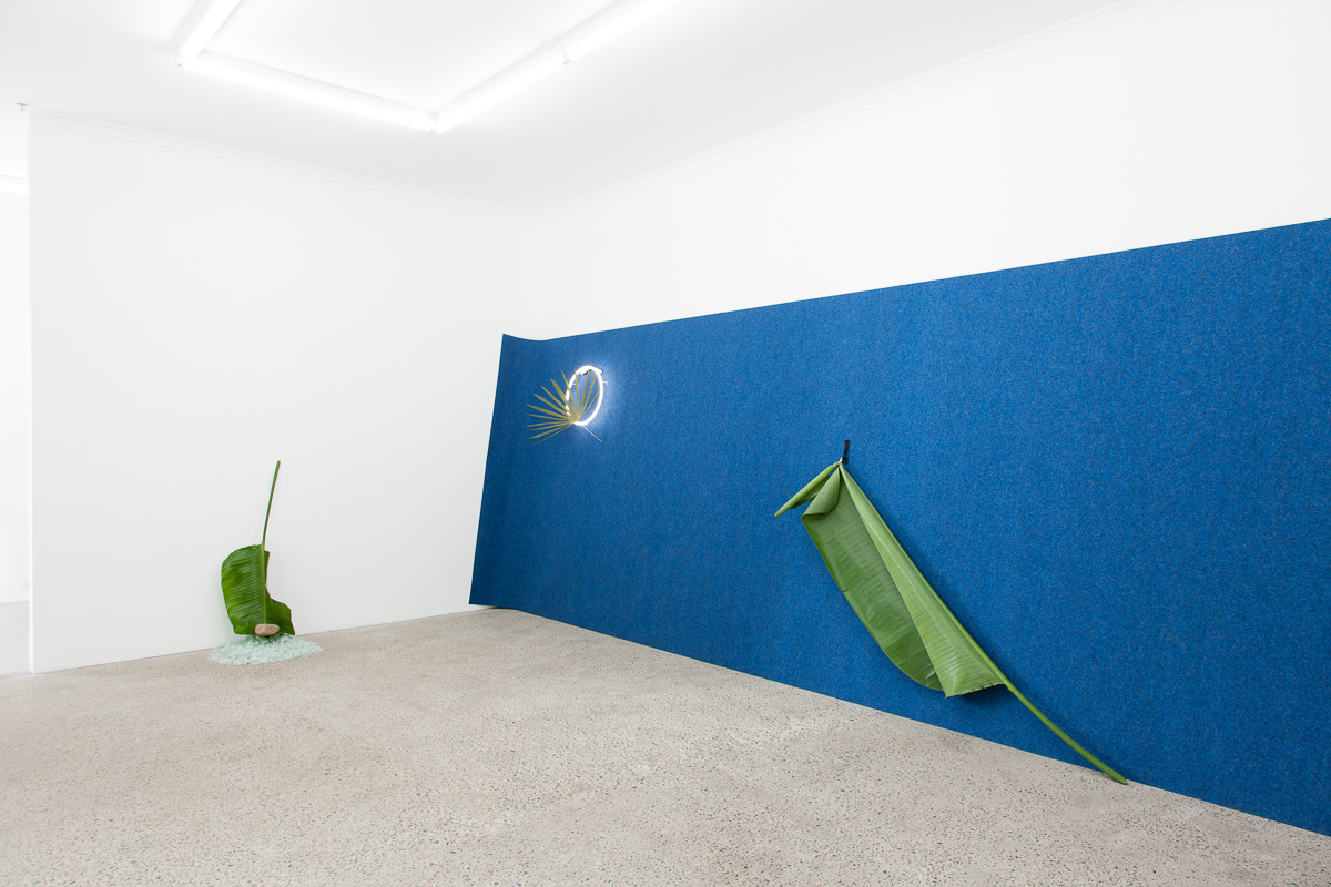 On the turning point of becoming and returning , 2016, Broken safety glass, rock, palm, carpet, neon, pressed palm, cock ring, Velcro, large palm, ipad, video from  Blue Hawaii  (1961), safety glass, rock, leaf. Photography: Docqument
