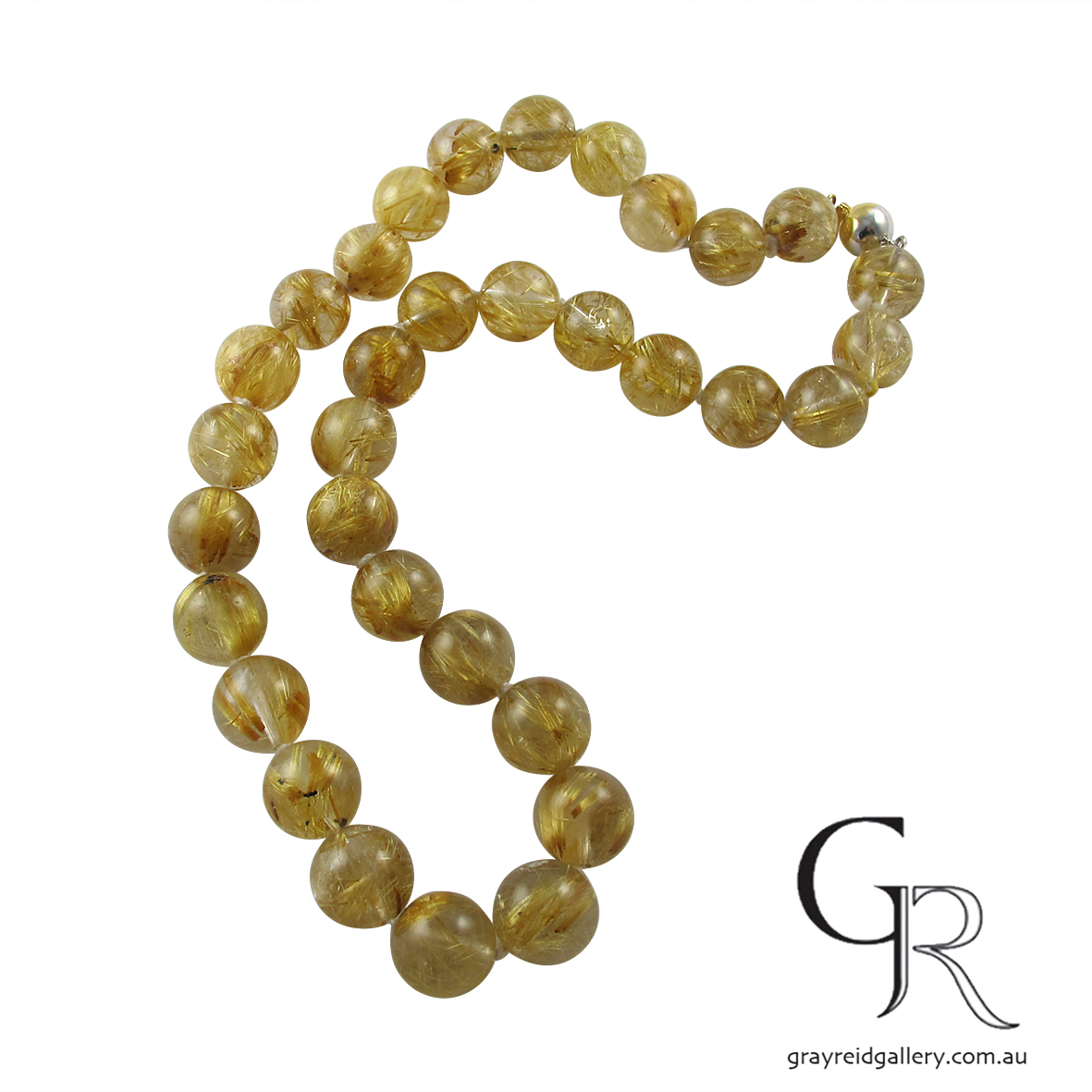 Strand of golden rutile 10mm beads on show at Gray Reid Gallery