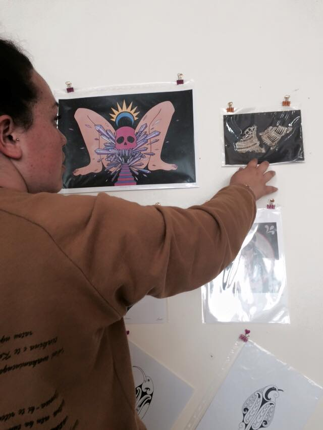 18 year old artist Kaea Graham hanging works for phase two of Toi Wāhine.