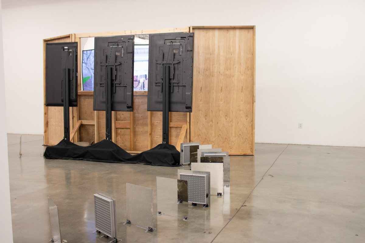 """""""Untitled Mirage 2, or an Exhibitionary Complex (The Lynda and Stewart Resnick Cultural Center)"""" Wood Structure, One Way Mirror, Sandbags, Three Channel Video Installation. 2017 work in situ, completed 2018."""