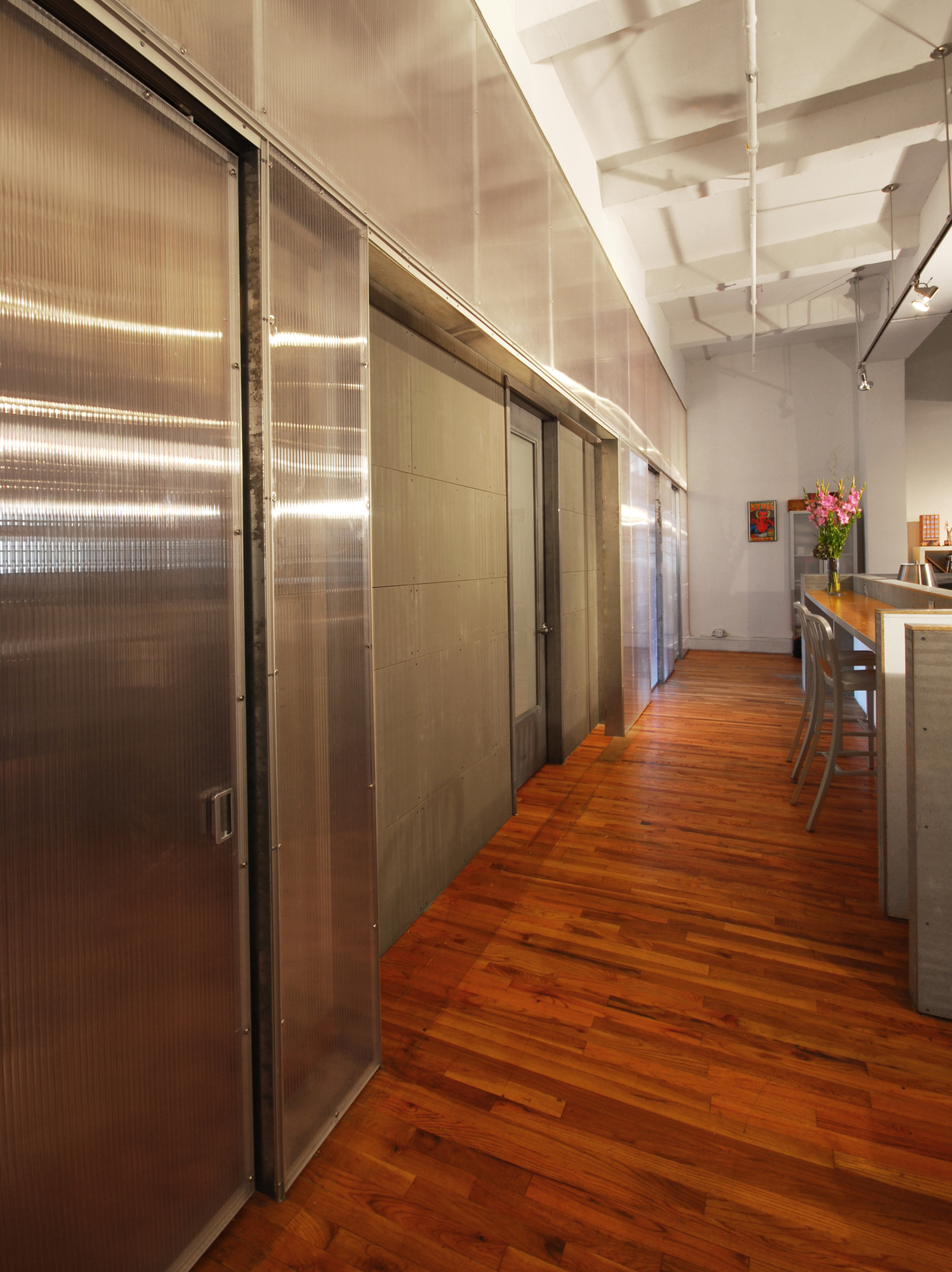 TRANSISTOR STUDIOS . New York, NY       This bi-coastal company specializes in post-production video editing for major market advertisers.  The New York office was undergoing the 3rd expansion of its existing space.  Previous additions were done haphazardly, without much consideration of efficient layout and positive staff interaction.  The main design exercise was to re-think the layout, incorporate the additional space the office was gaining, and establish a consistent identity.       Staff seating was consolidated and separated from client circulation, yet remains at the heart of the office between producers and directors.  This low budget project called for an innovative use of materials to help give the office an identity.  In lieu of a standard gypsum board partition wall, a translucent polycarbonate screen was created that gives privacy to the producers, while allowing natural light to filter into the staff area.          Cement board, typically used for backing ceramic tile, was utilized as a cladding material for the solid edit suite that appears to be floating behind the translucent panels.  This solution created an easily identifiable destination for their clients that was also provided the required sound isolation from the rest of the office.       The lounge was designed with simple, modern furnishings that are comfortable and clean, keeping with the office's newfound aesthetic.     All photos © STUDIOrobert jamieson