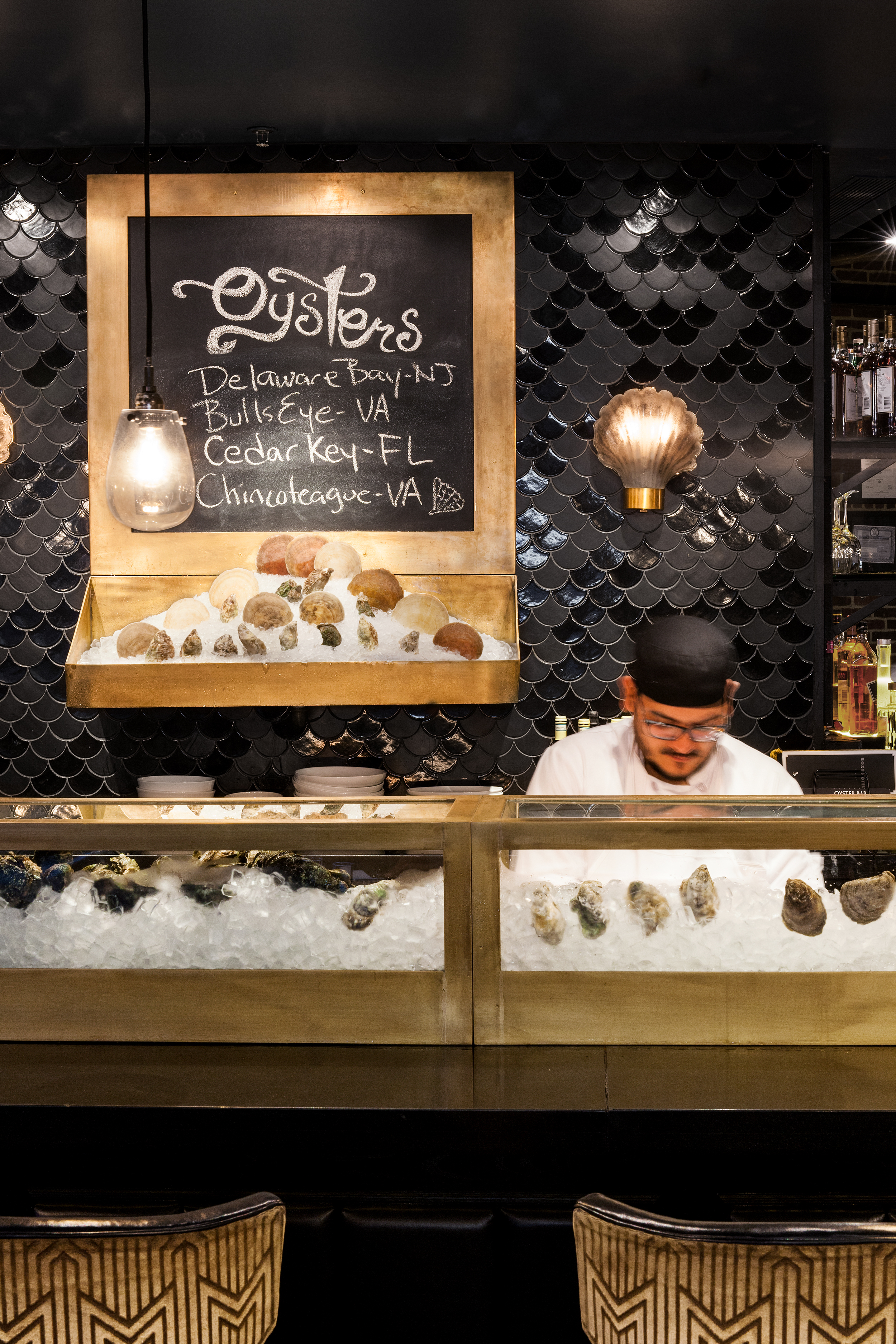 ROXY OYSTER BAR and CONCESSION    New York, NY    The Roxy Hotel in TriBeCa hired us to help realize a radical transformation of their public amenity spaces within the hotel. STUDIOjamieson took several under-utilized spaces and transformed them into branded programming within the hotel.  We first inserted  Jack's Stir Brew Coffee  into a former egress bay of the facade.  We were then commissioned to create a new Oyster Bar within the existing lobby restaurant area and a new concession stand to service their basement art-house cinema.    The Oyster Bar features custom brushed brass cold display cases, vintage clam-shell lighting sconces and Moroccan fish-scales mosaic tile.    The Concession stand features a custom curved wood and glass display case to compliment the existing cinema lobby geometry.  The neon cinema sign was salvaged and retrofit to serve as the new menu board.  Theater style lighting was added to complete the look.     All photography © Heidi's Bridge