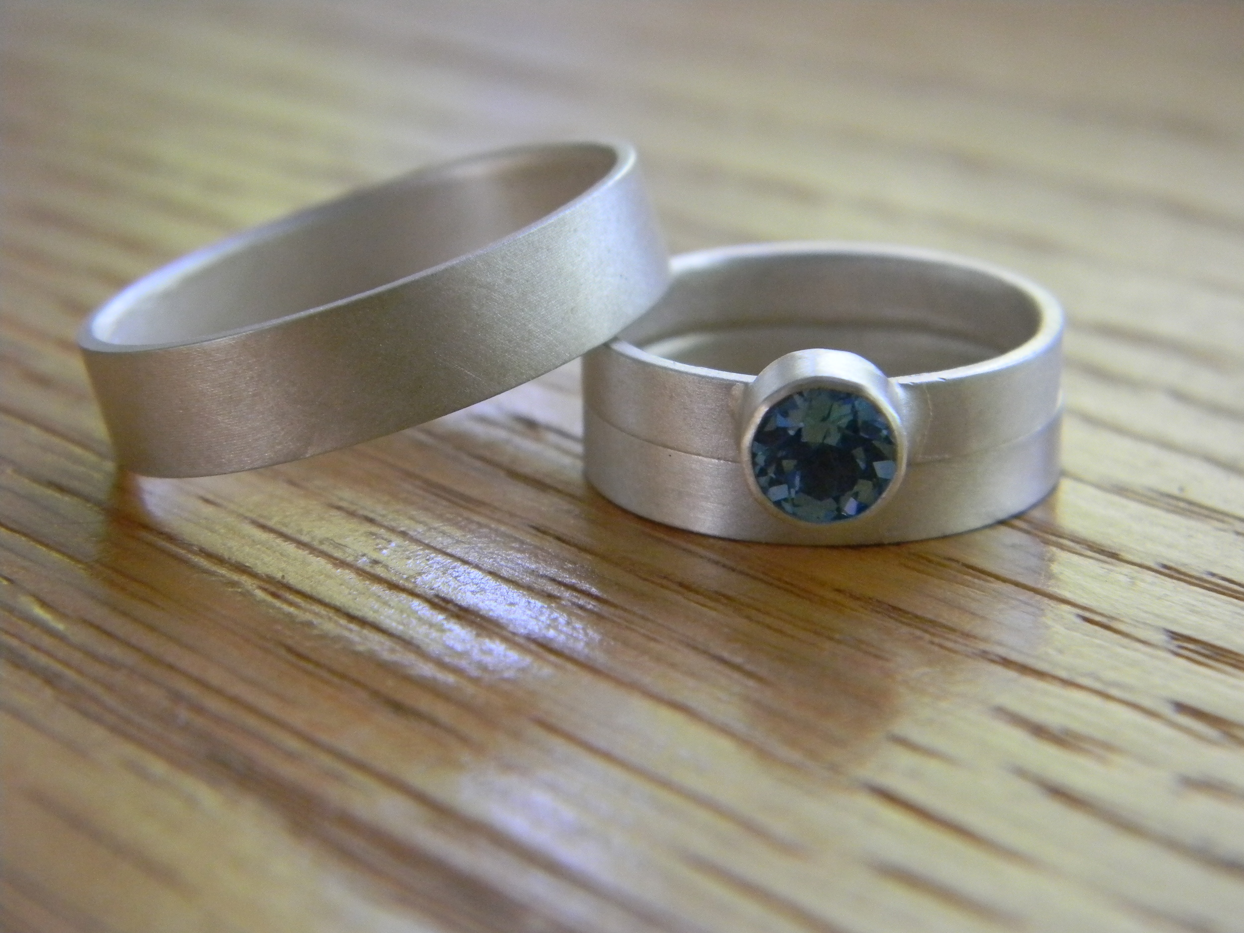 Sterling silver bands with a  matte finish.  Engagement band features a 5 mm round faceted swiss blue topaz