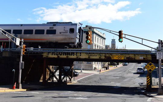 A NJ Transit passenger train passes over the train bridge at the Garfield Train Station