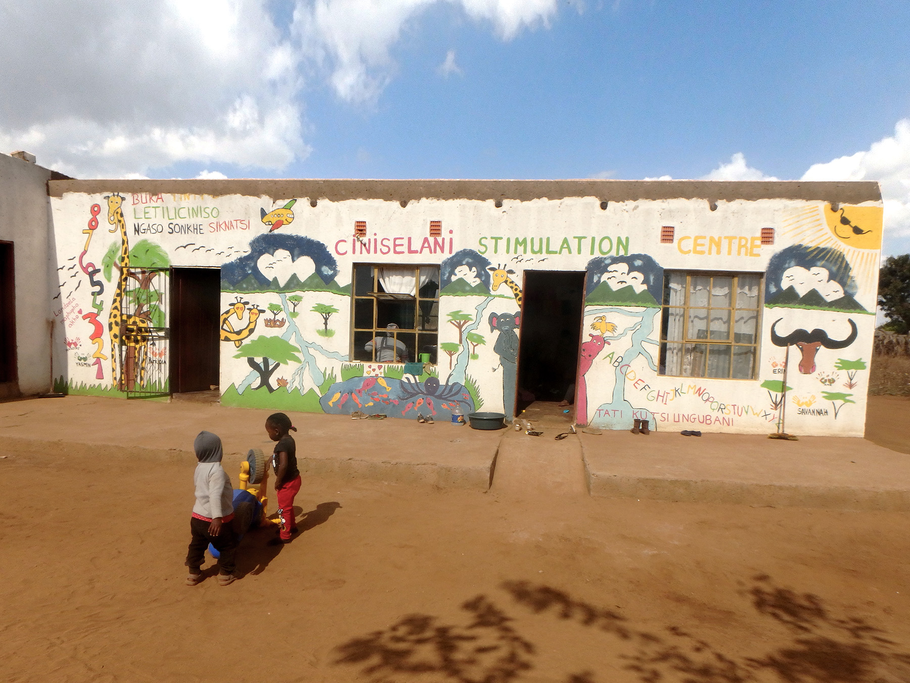The inaugural group of volunteers recently painted the main facade with symbols of Africa.  Ironically, most of these children will never get the opportunity to see a wild giraffe, mountains, or an airplane.