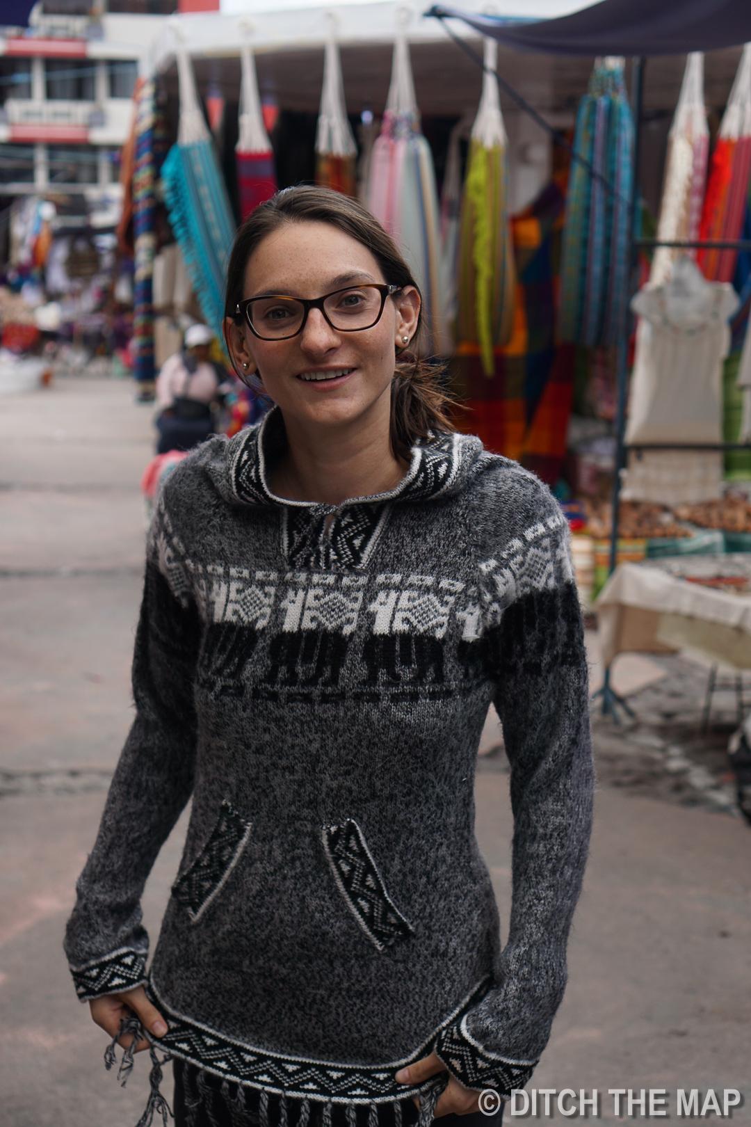 Sylvie tries on an alpaca sweater in Otavalo, Ecuador