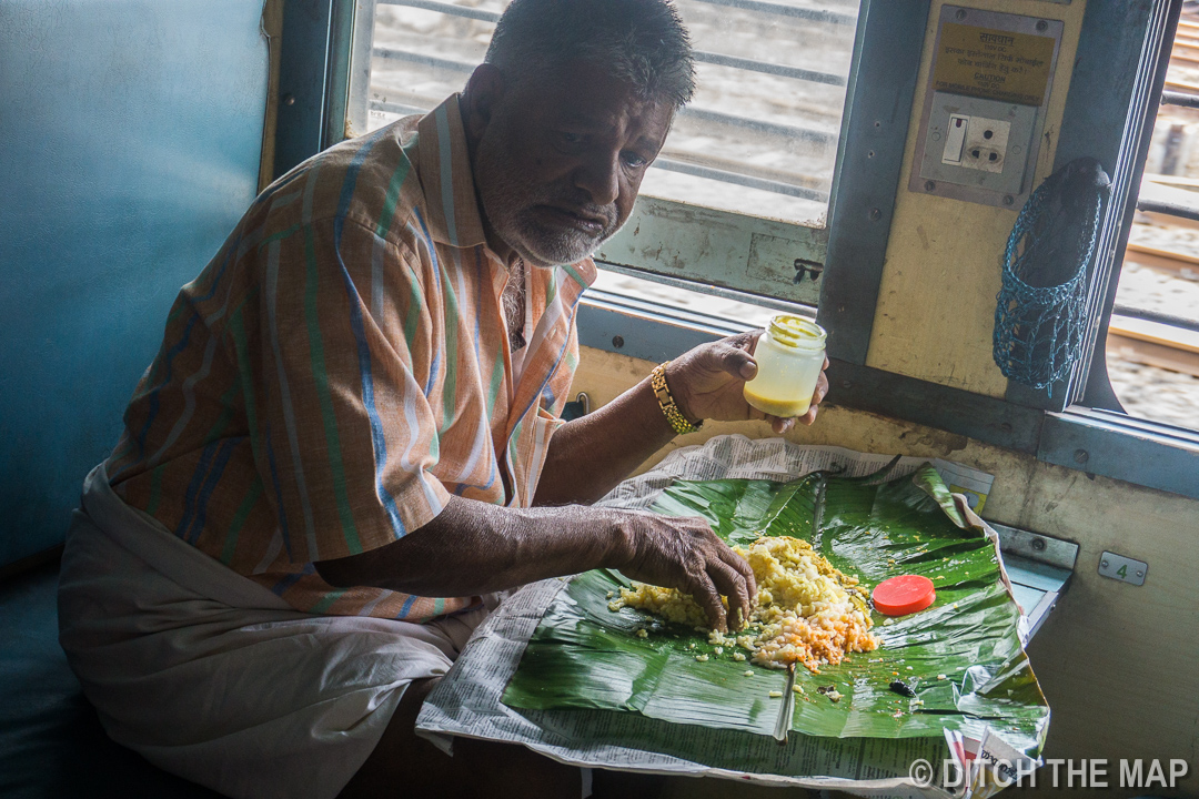 Indian Eating with his Hands on a Train in Kerala, India