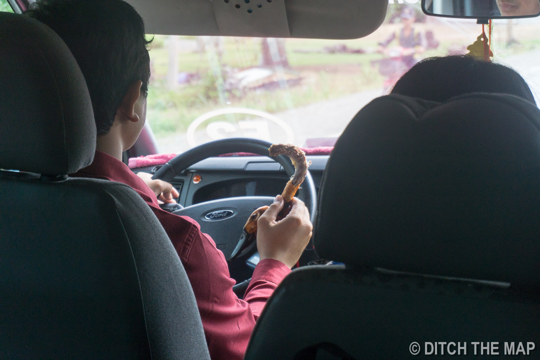 Our Driver Eating a Duck Neck While Driving to Kampot, Cambodia