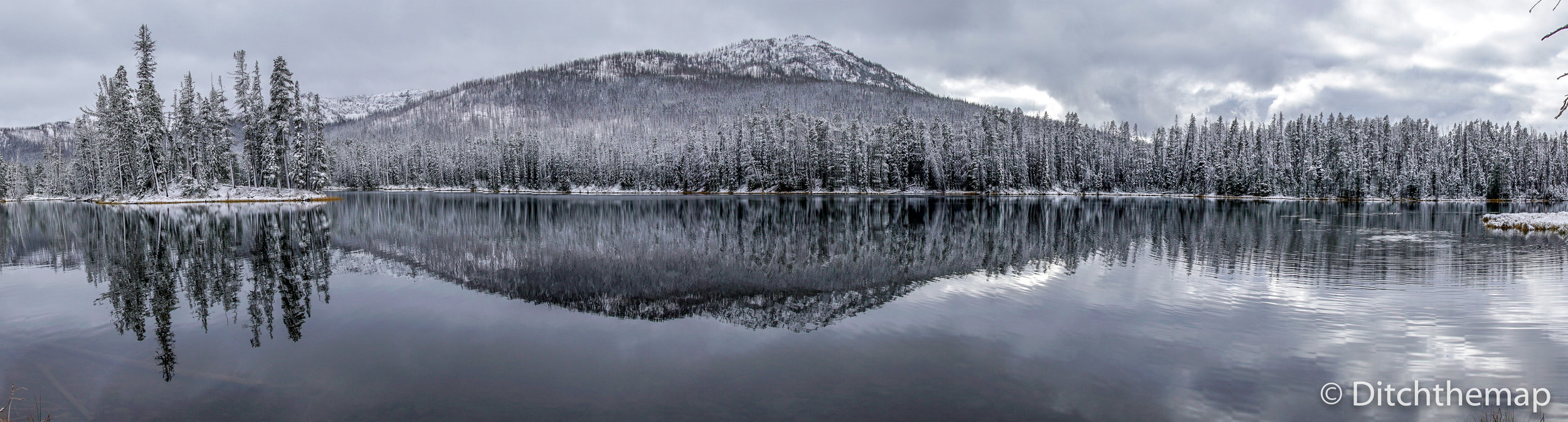 Light snow covered strees and mountain with reflection on lake