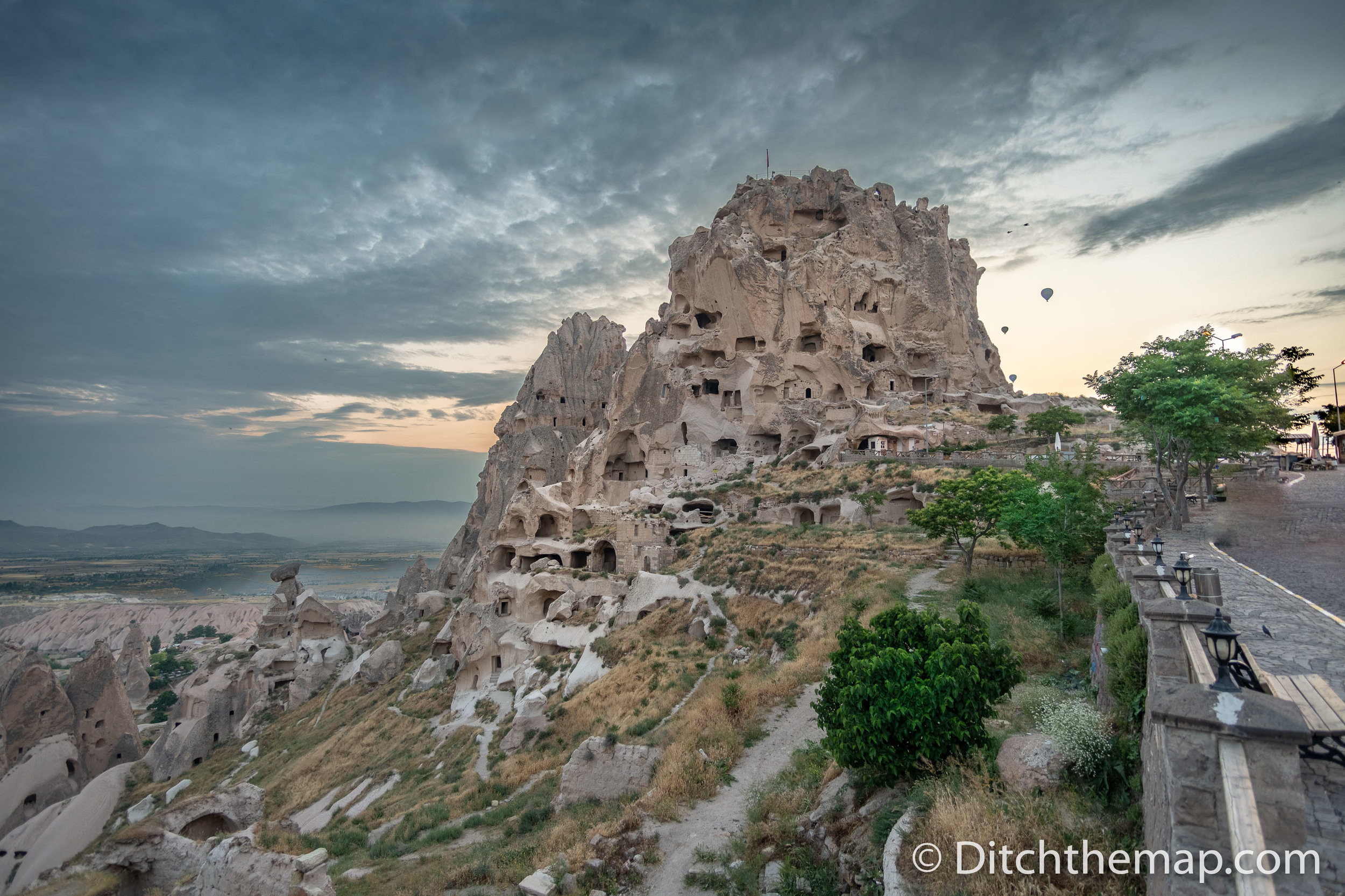 Uchisar Castle in Cappadocia, Turkey with balloons in background