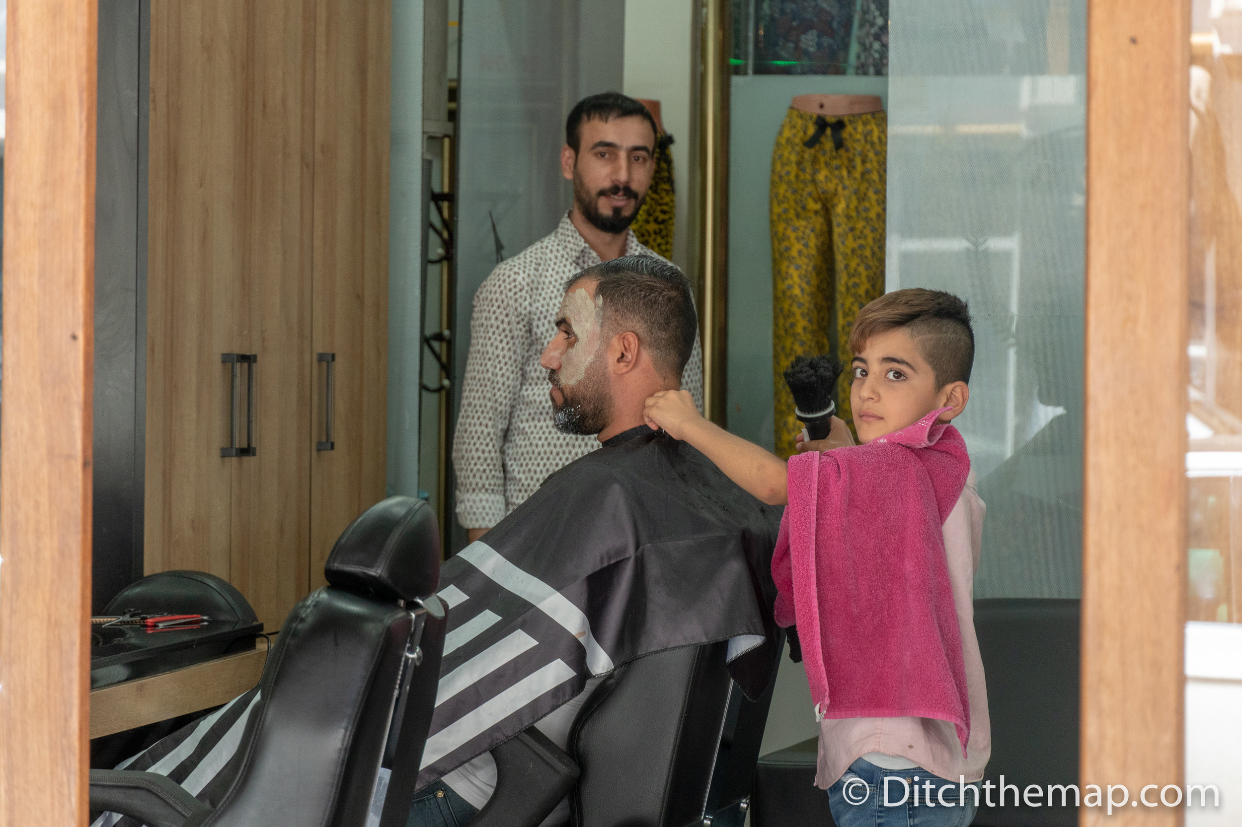 Boy shaving a man at barber in Diyarbakir