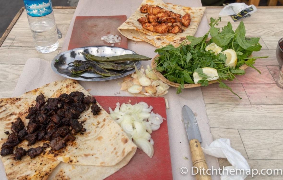 We eat dalak (lamb spleen) kebab and chicken kebab for dinner near the Gumruk Bazaar in Sanlirufa, Turkey