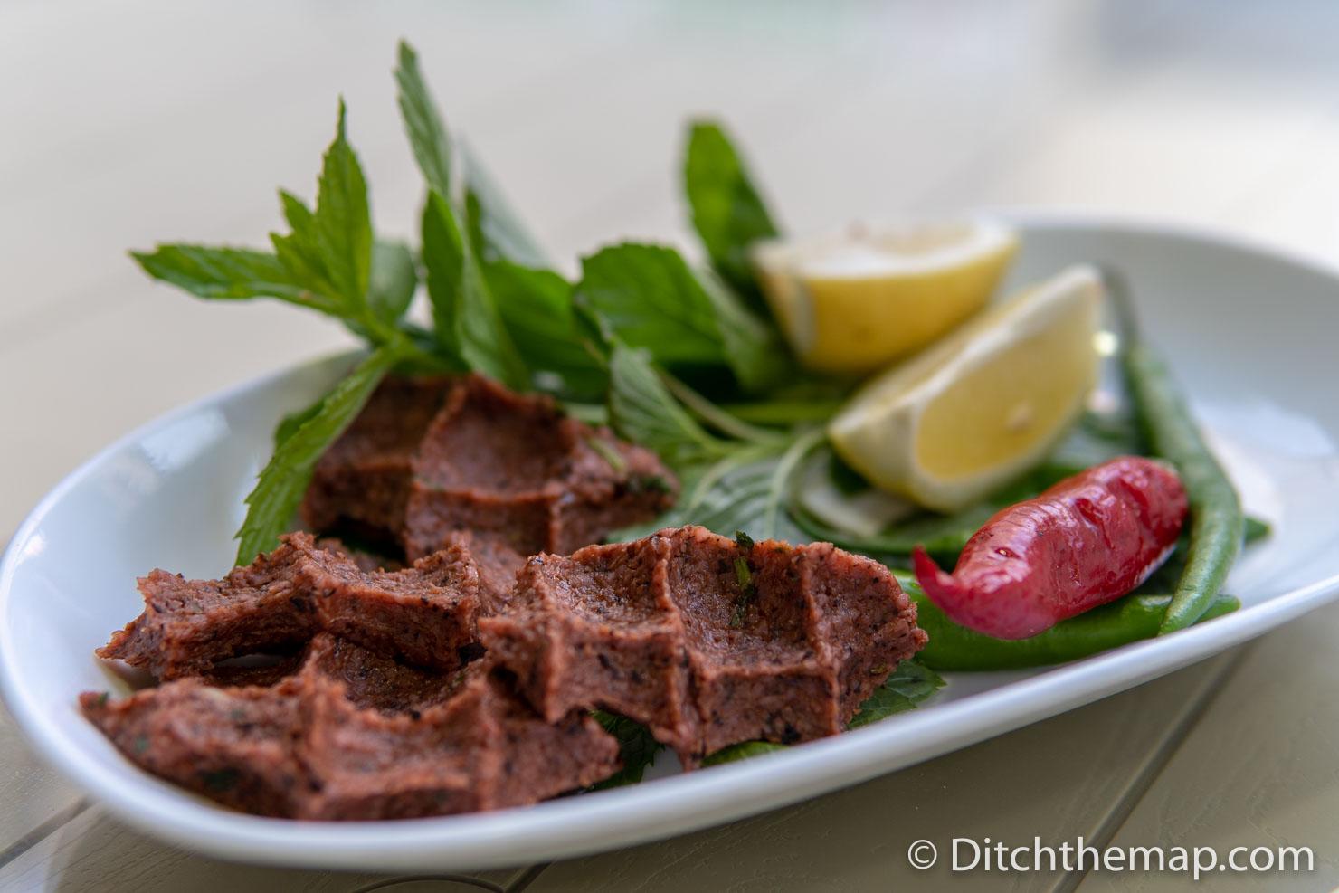 A plate of cig kofte - meat-free, spicy, bulgur meatballs, in Sanliurfa, Turkey