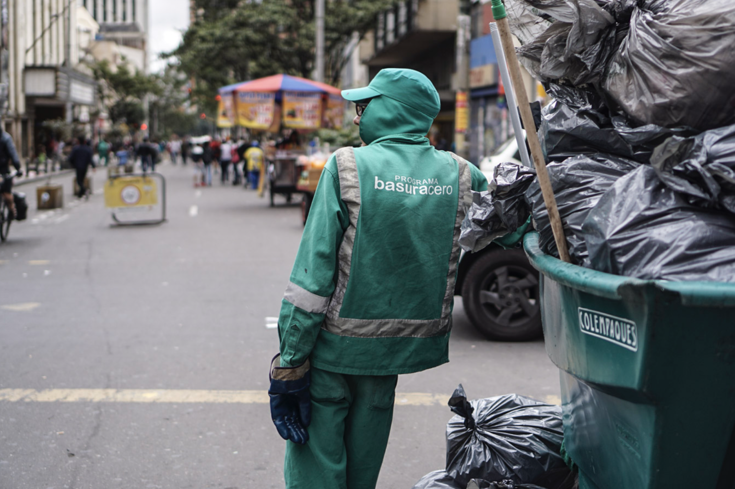 Man stands by piles of garbage