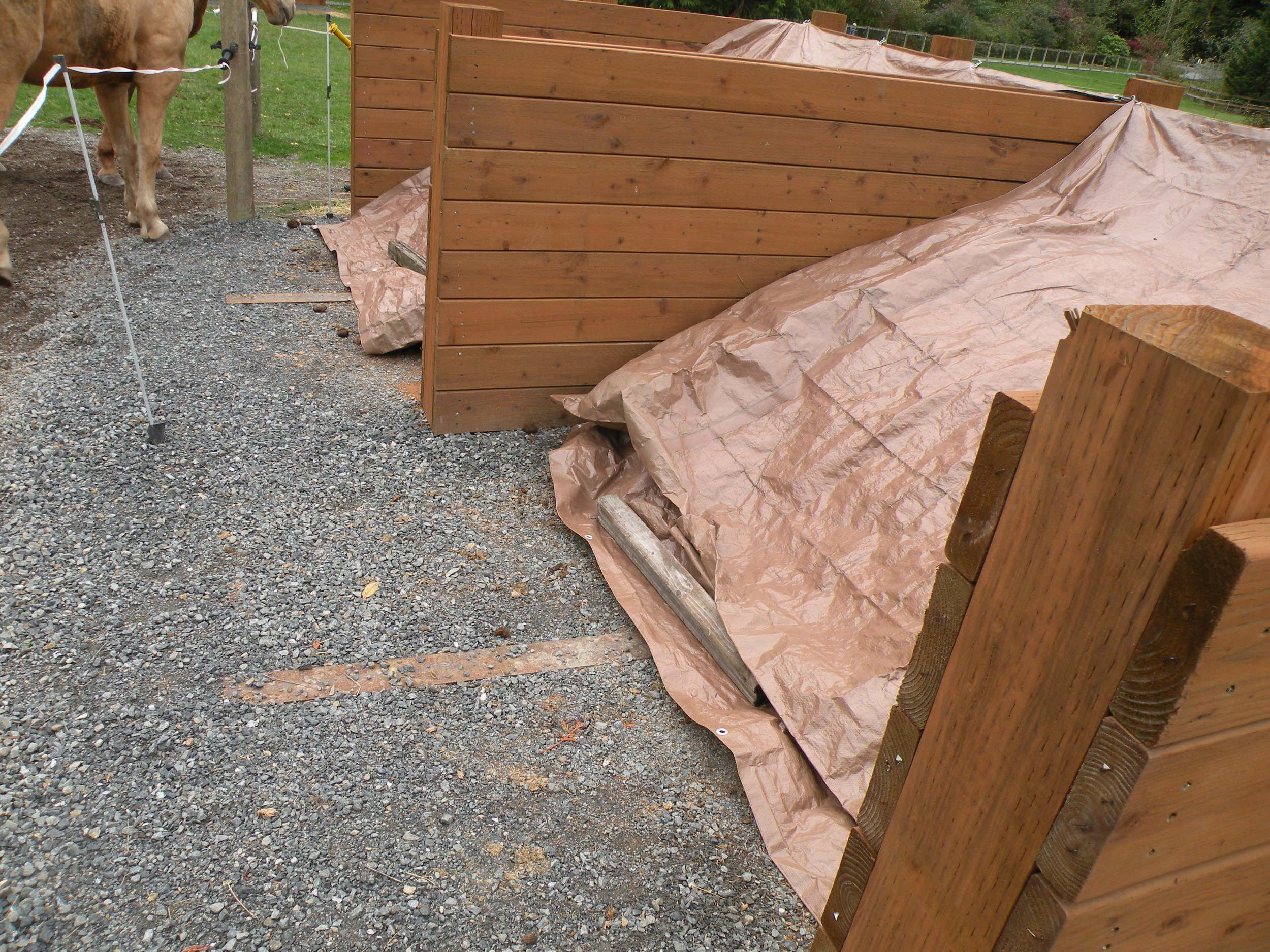 Covering your manure piles can be as easy as adding tarps and weighing them down with boards or bricks.