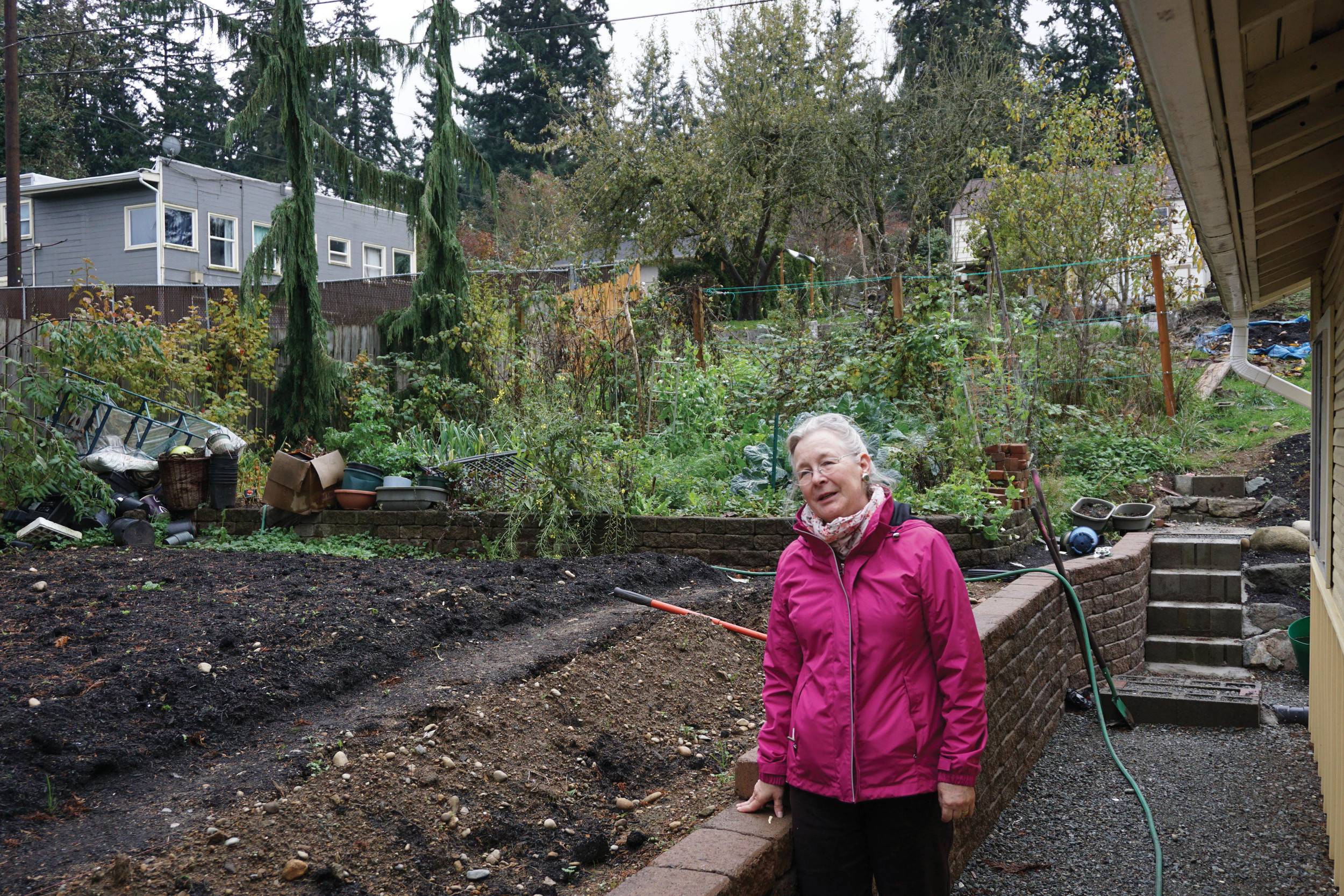 Chris Martinez stands beside a new retaining wall and the garden area created with soil from excavation around her buildings.