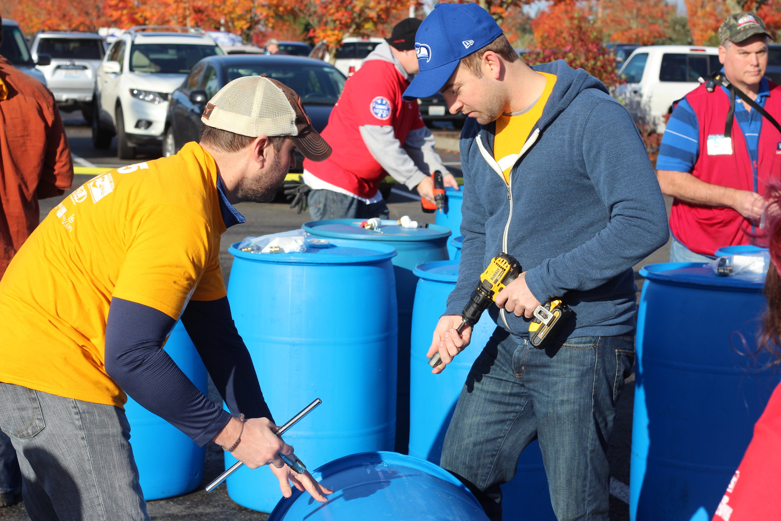 Volunteers drill and thread holes into recycled food-grade barrels.