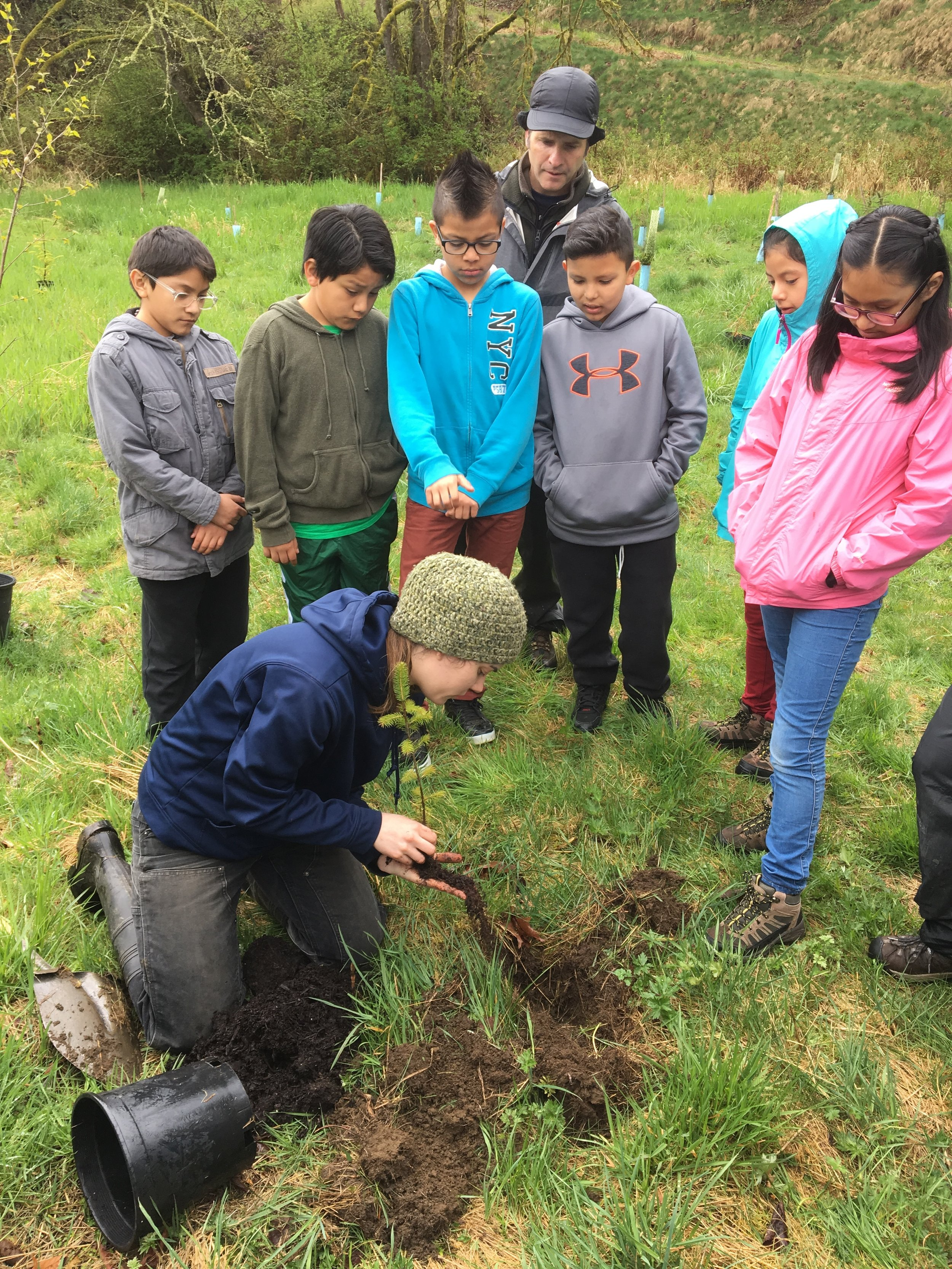 SCD's Restoration Project Coordinator (WCC), Ashley Shattuck demonstrates tree planting to a group of students.