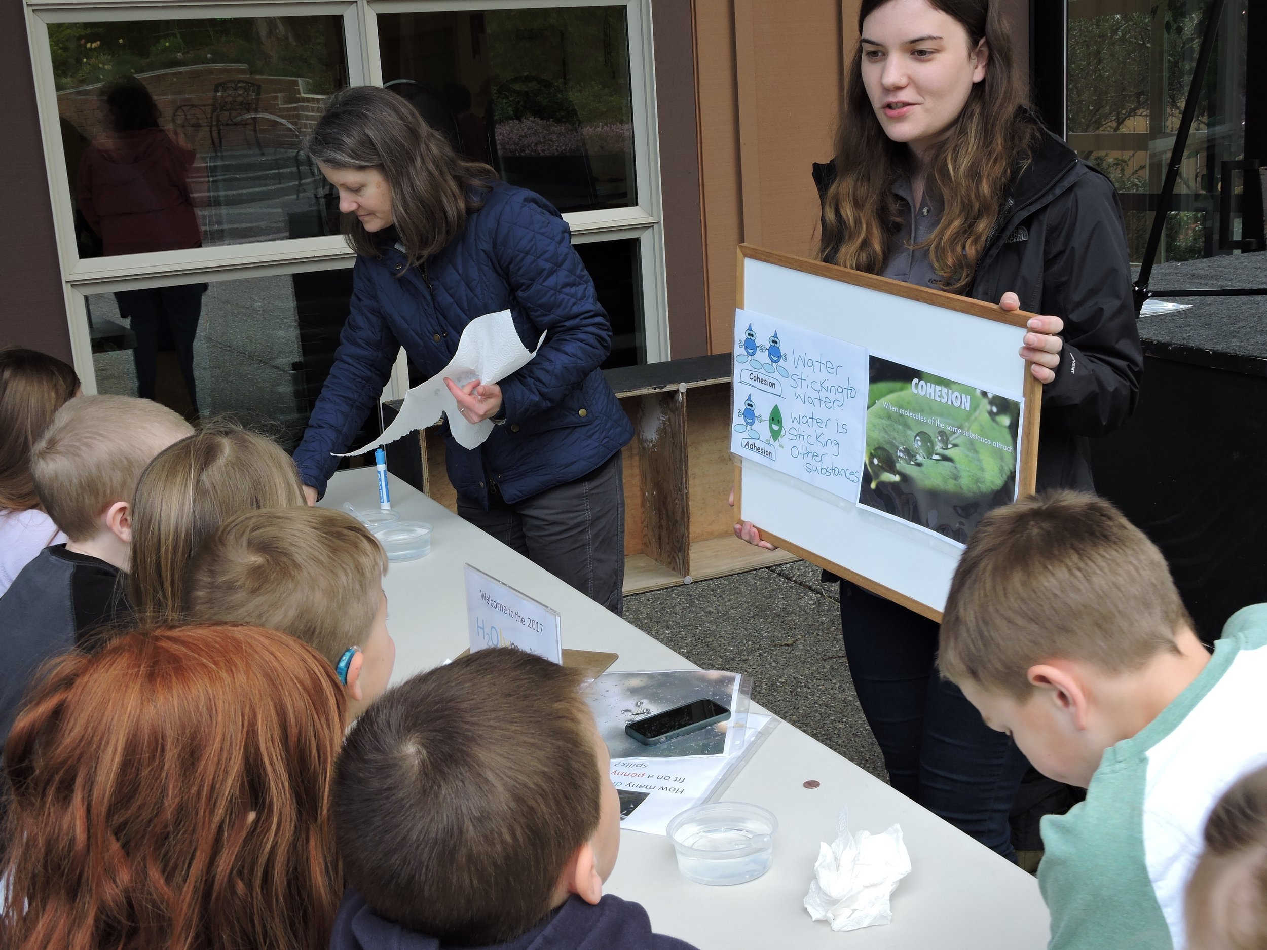 Ashley Shattuck, WCC Restoration Specialist and Kathryn Wells teach students about water cohesion and adhesion before they begin balancing water drops on a penny to see cohesion first-hand!