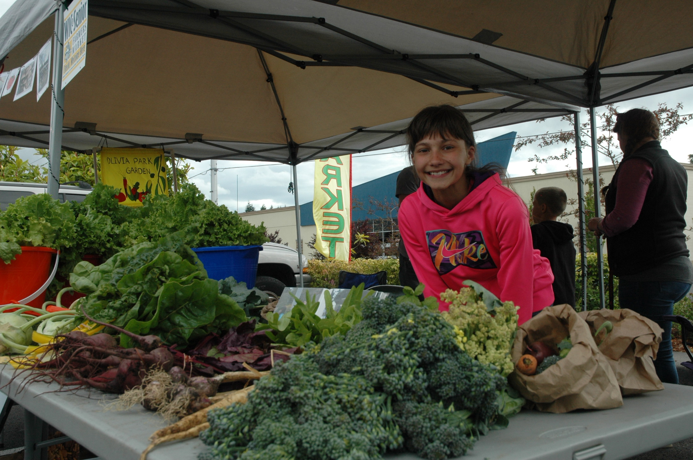 Diana Cantini poses with produce grown in her school garden that they brought to their local farmers market.