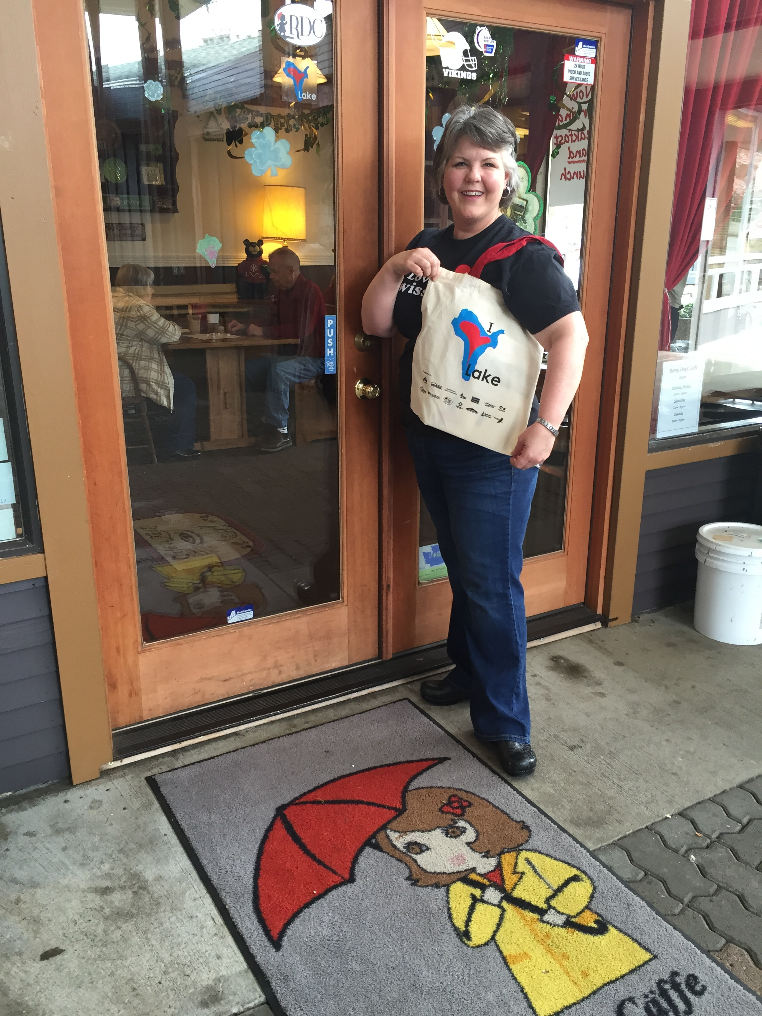 Rainy MacDuff poses with an I Love Lake tote bag outside of her cafe.