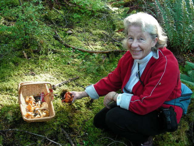 Barbara poses in the forest with a basket of chanterelle mushrooms.