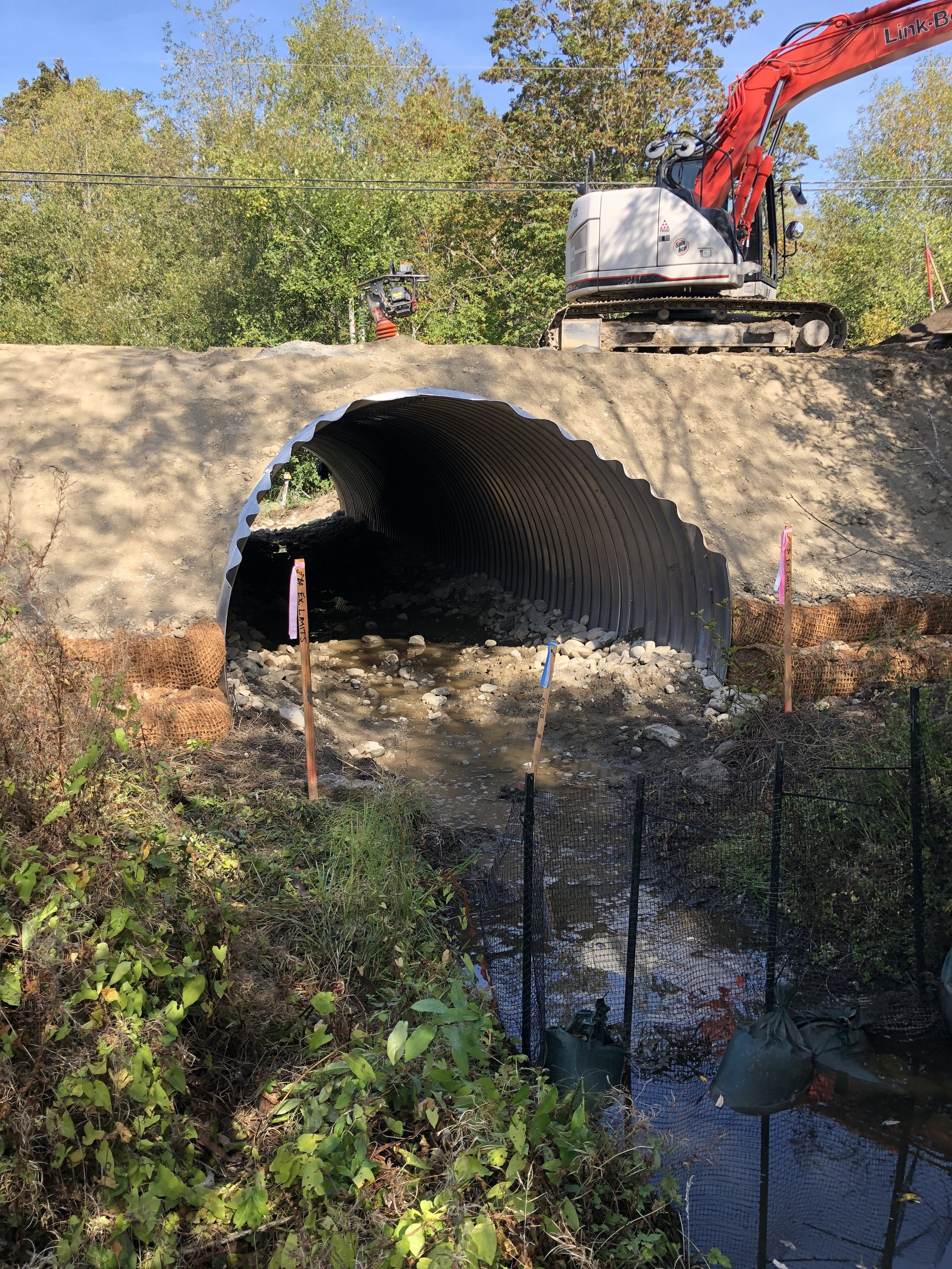 In this photo you can see the placed culvert, fully surrounded with backfill materials and the coir lifts for stability.