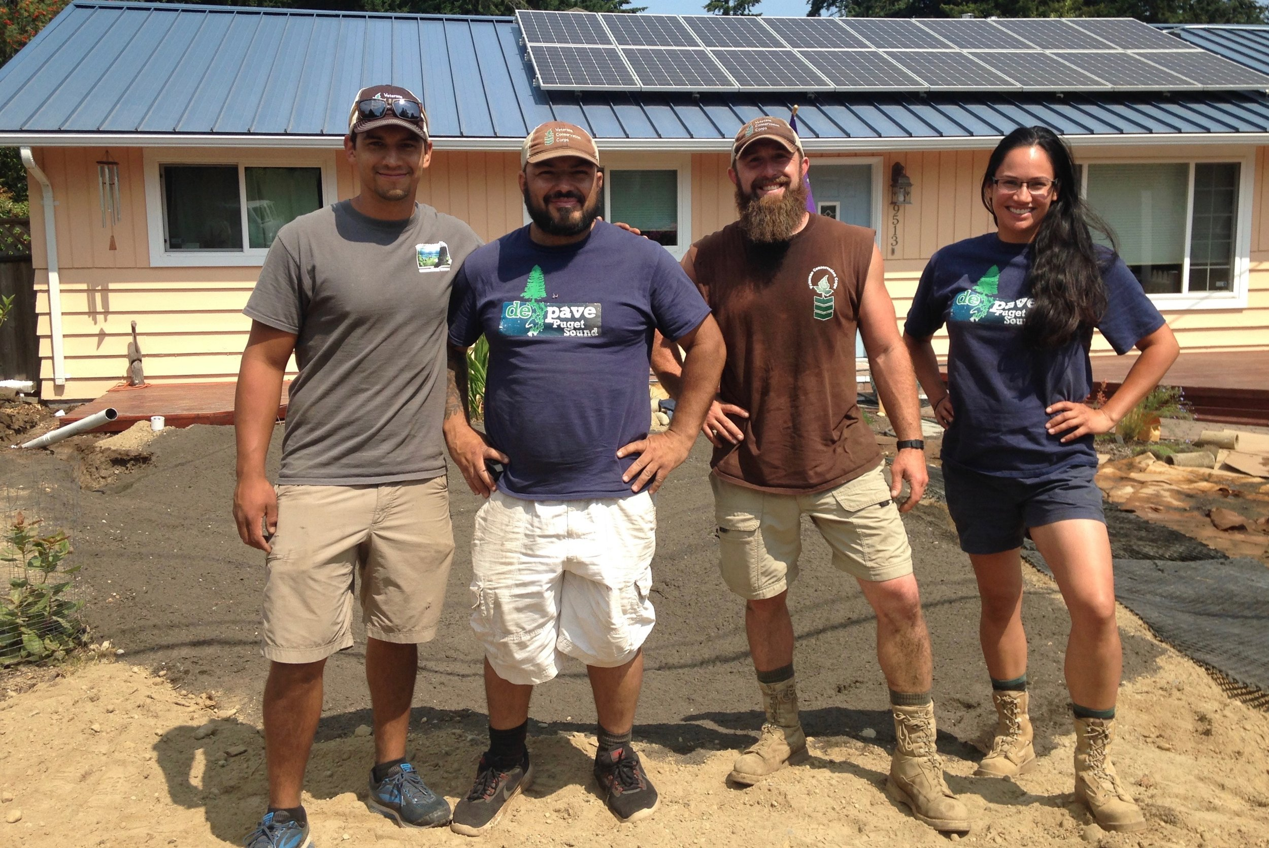 Cameron Coronado (Vet Crew Program Manager), Chris Rodriguez (Vet Crew Supervisor), Taylor Pesce (former Vet Crew Member), and Sara Rocero (former Vet Crew Member and active Americorps Restoration Assistant) at a homeowner's property in Edmonds during rain garden construction.